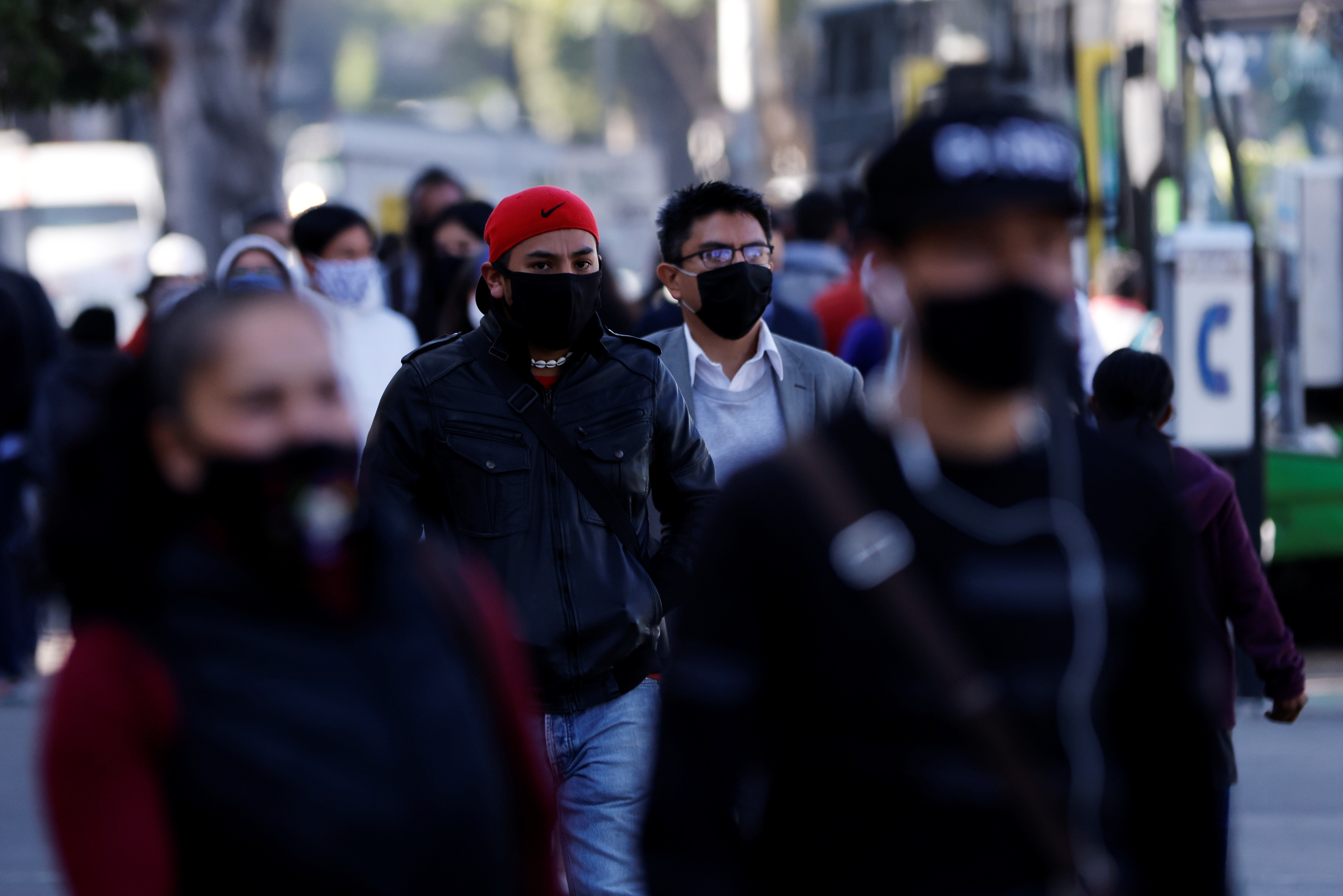 People wearing face masks walk on the street, as the coronavirus disease (COVID-19) outbreak continues, in Mexico City, Mexico.