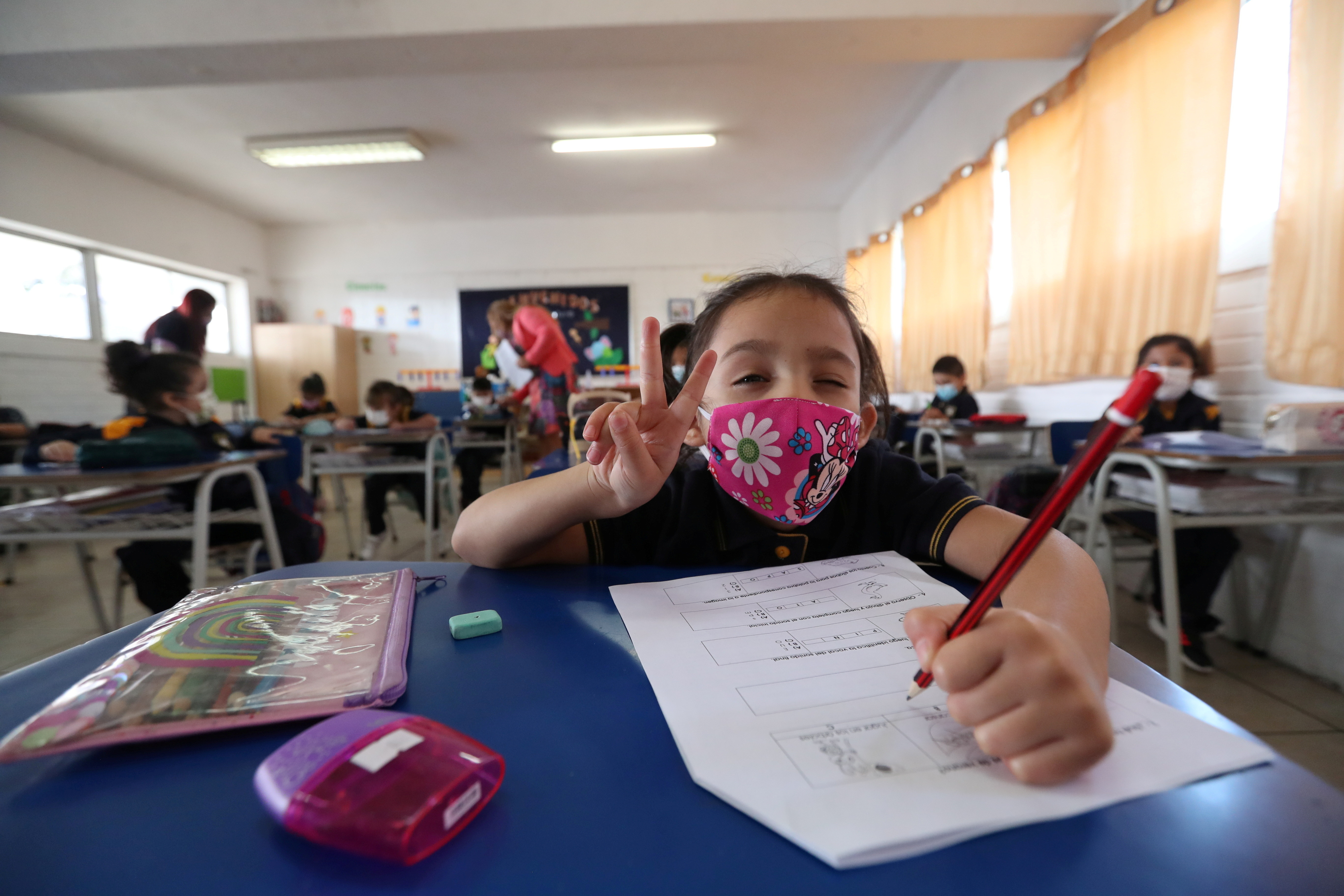 A student gestures with a face mask on in a classroom at a primary school.
