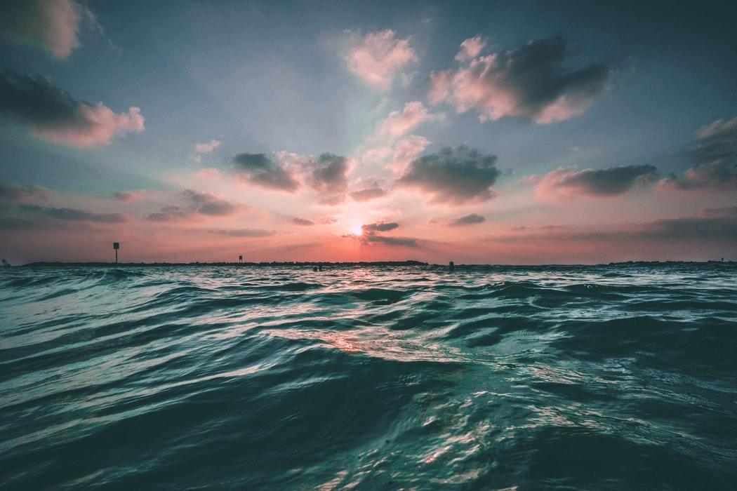 A photo of an ocean with the sun setting in the background.