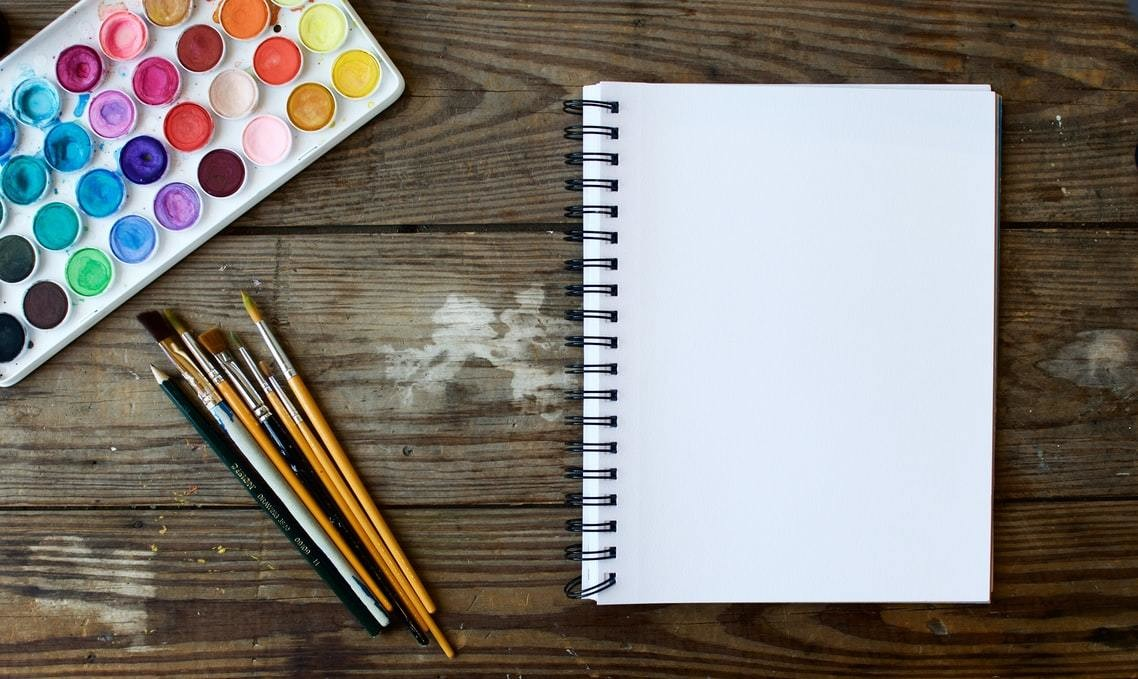A blank notepad, situated next to paintbrushes and paint
