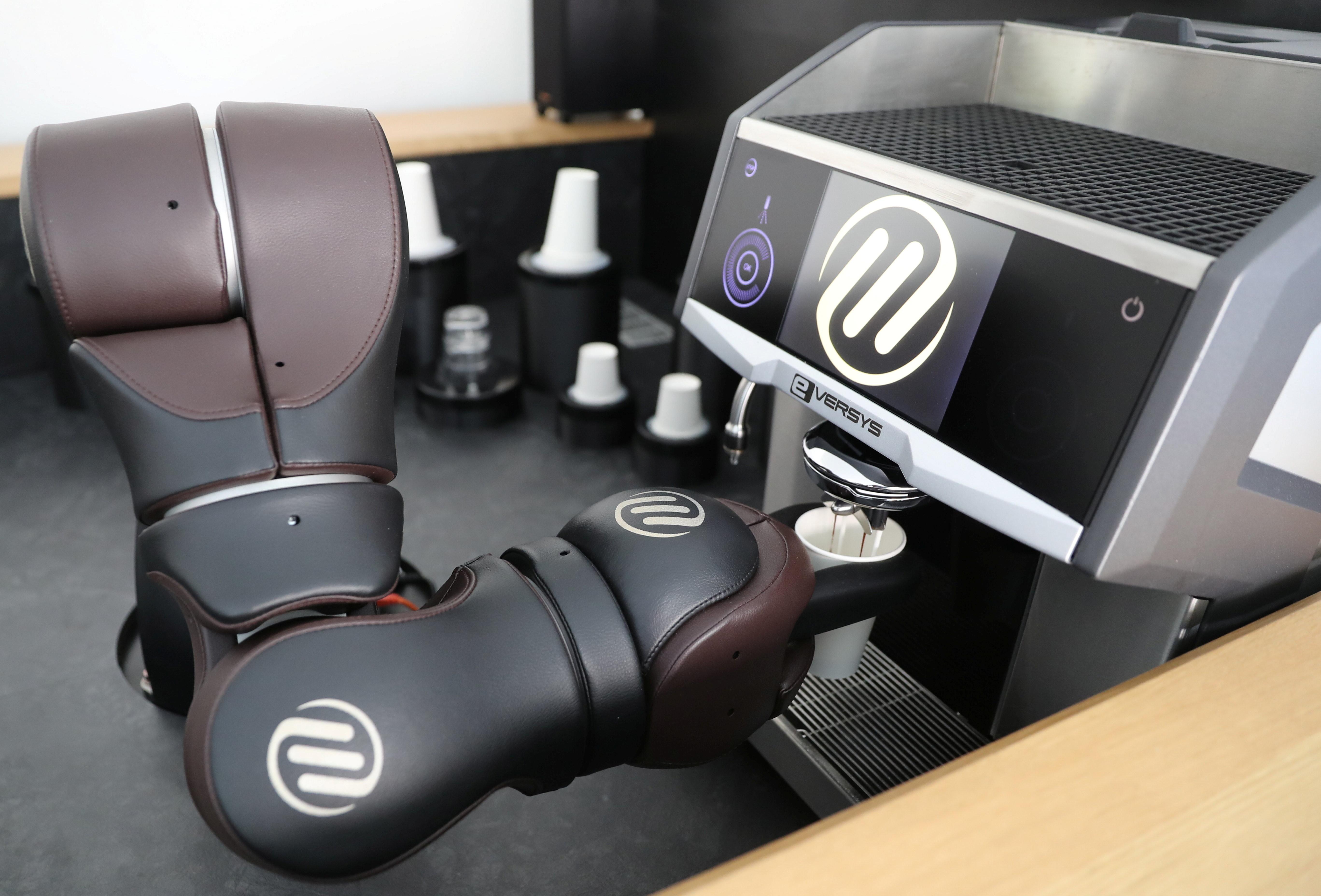 A robotic arm prepares a cappuccino at the Barney Barista Bar of the Swiss F&P Robotics company in Zurich, Switzerland
