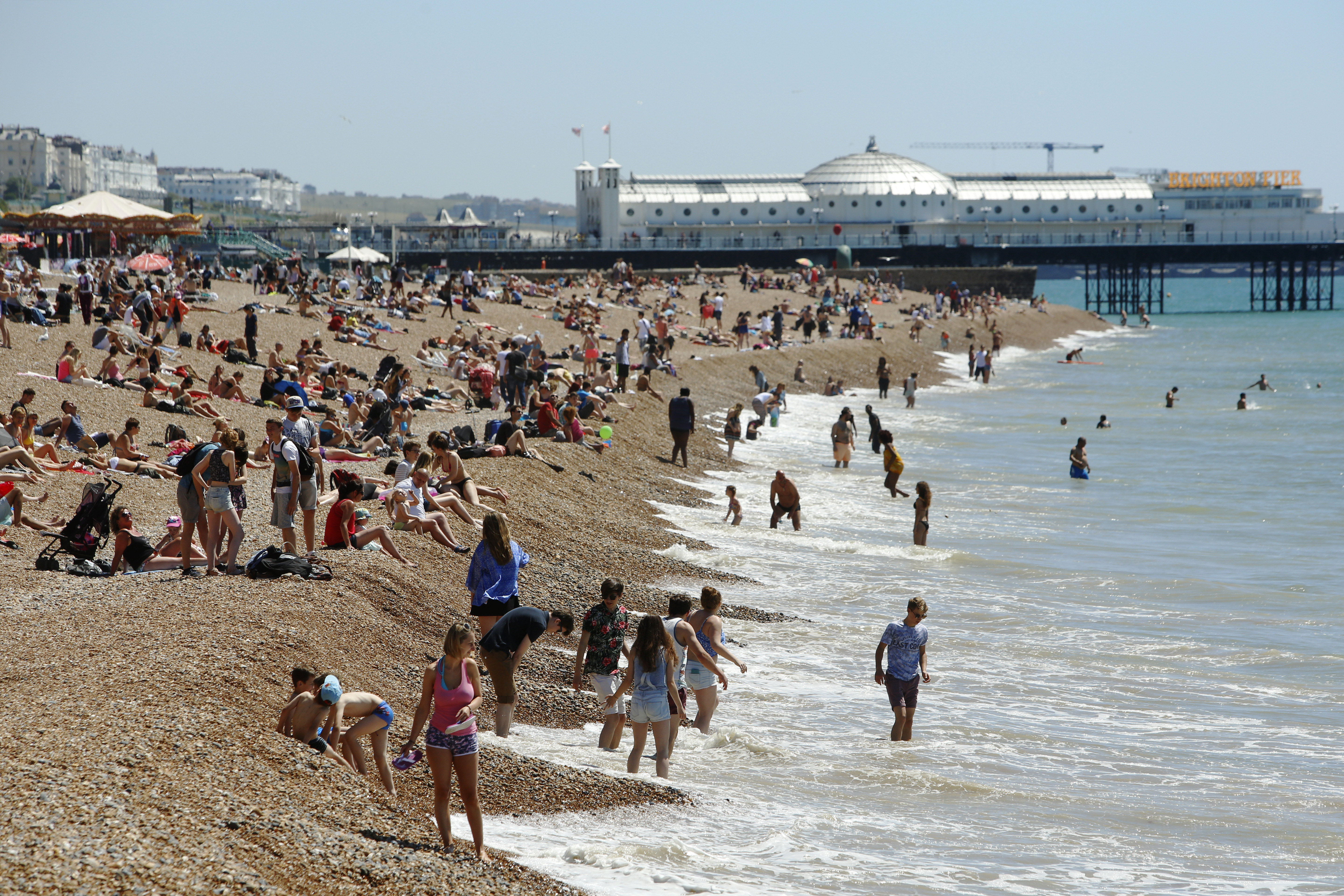 Sunbathers and swimmers enjoy a hot Summer day at Brighton beach in Britain June 30, 2015. Britain's Meteorological Office has warned of the possibility of heatwave conditions, with temperatures reaching their highest of the year on Tuesday and Wednesday.    REUTERS/Luke Macgregor   - LR2EB6U0ZPAD0