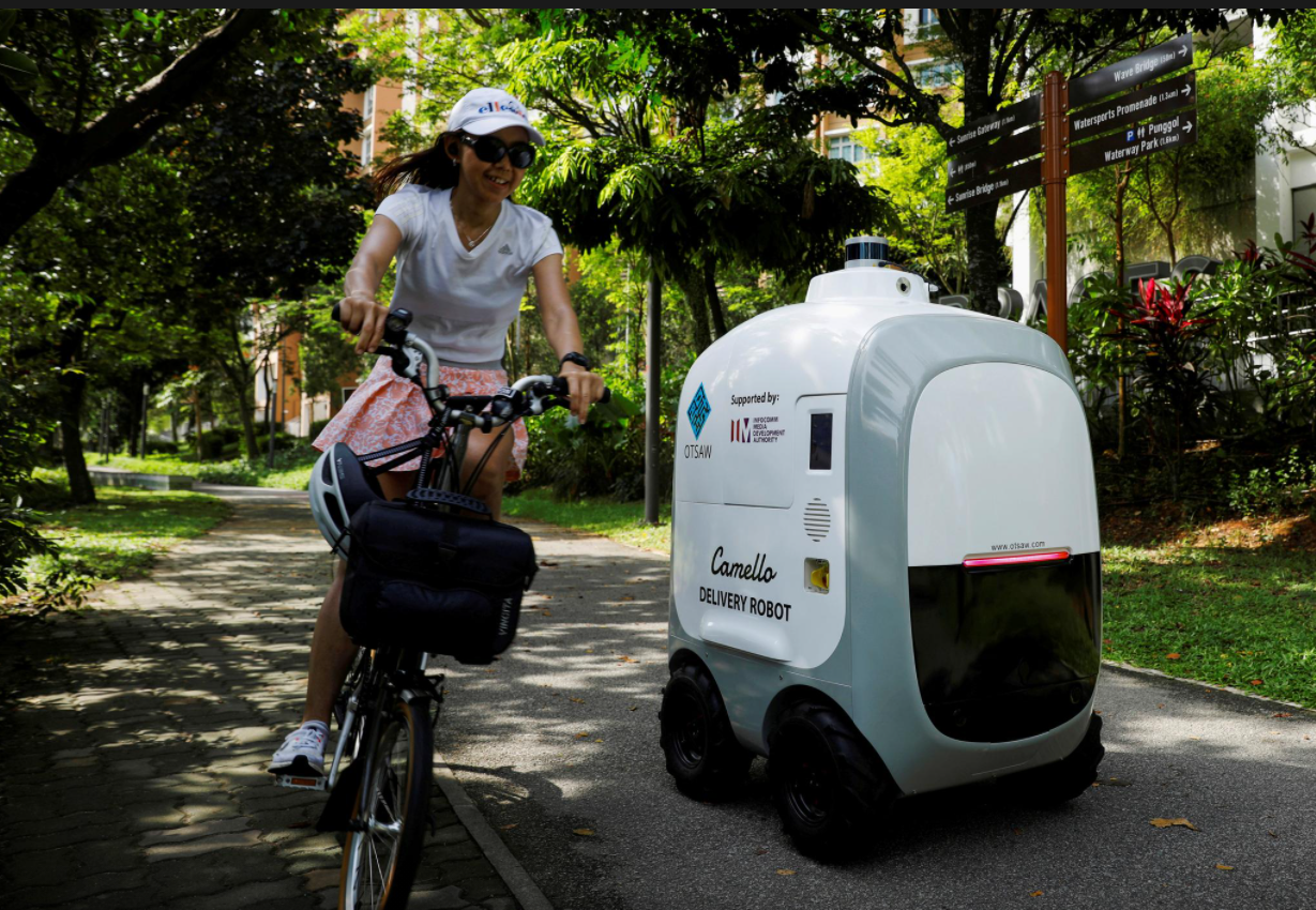 A cyclist passes as Camello, an autonomous grocery delivery robot, makes its way during delivery in Singapore.