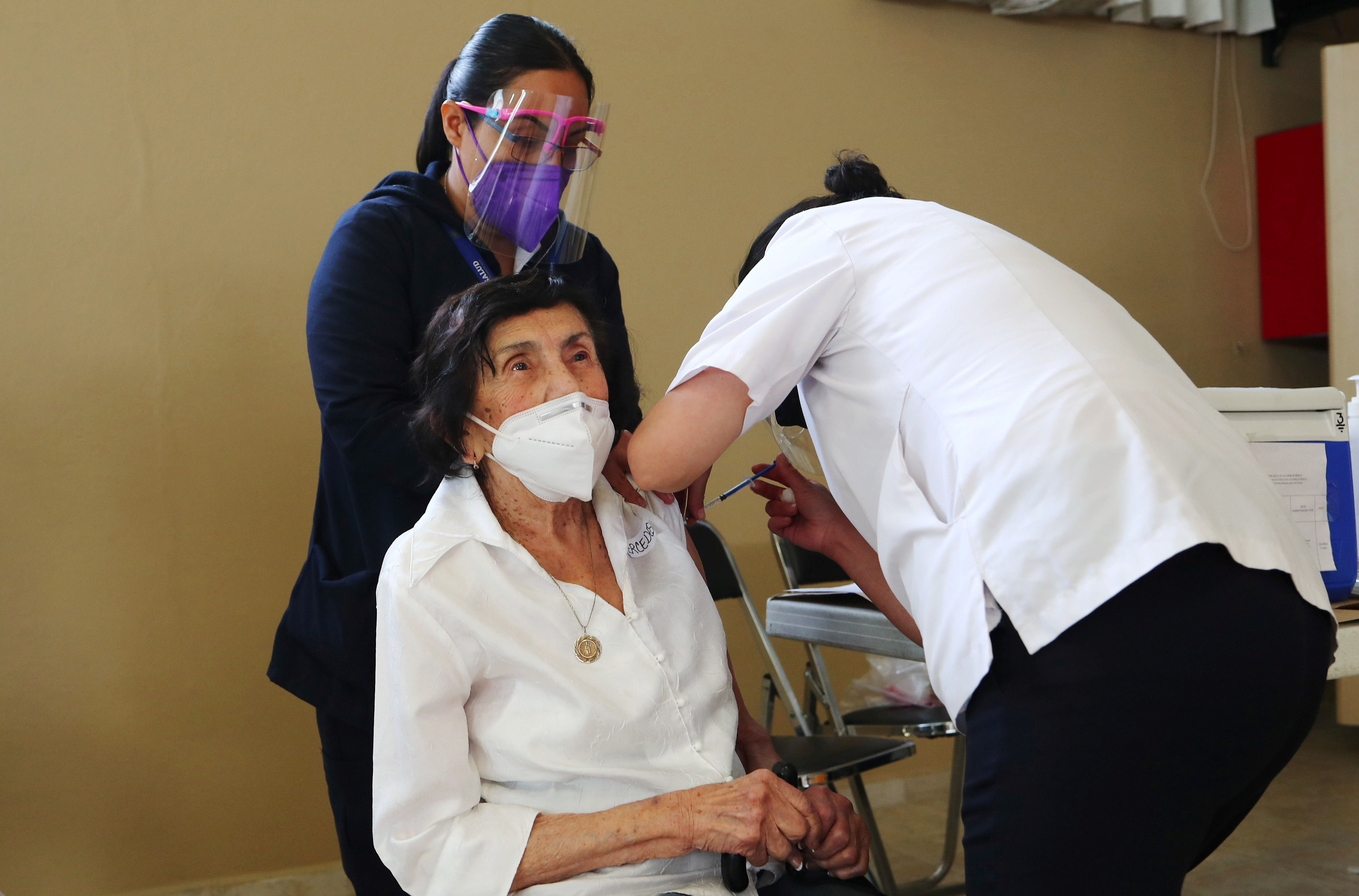 Health workers administer a dose of the AstraZeneca coronavirus disease (COVID-19) vaccine to an elderly woman, at a nursing home in Mexico City, Mexico, February 17, 2021. REUTERS/Henry Romero - RC2NUL9G44J5