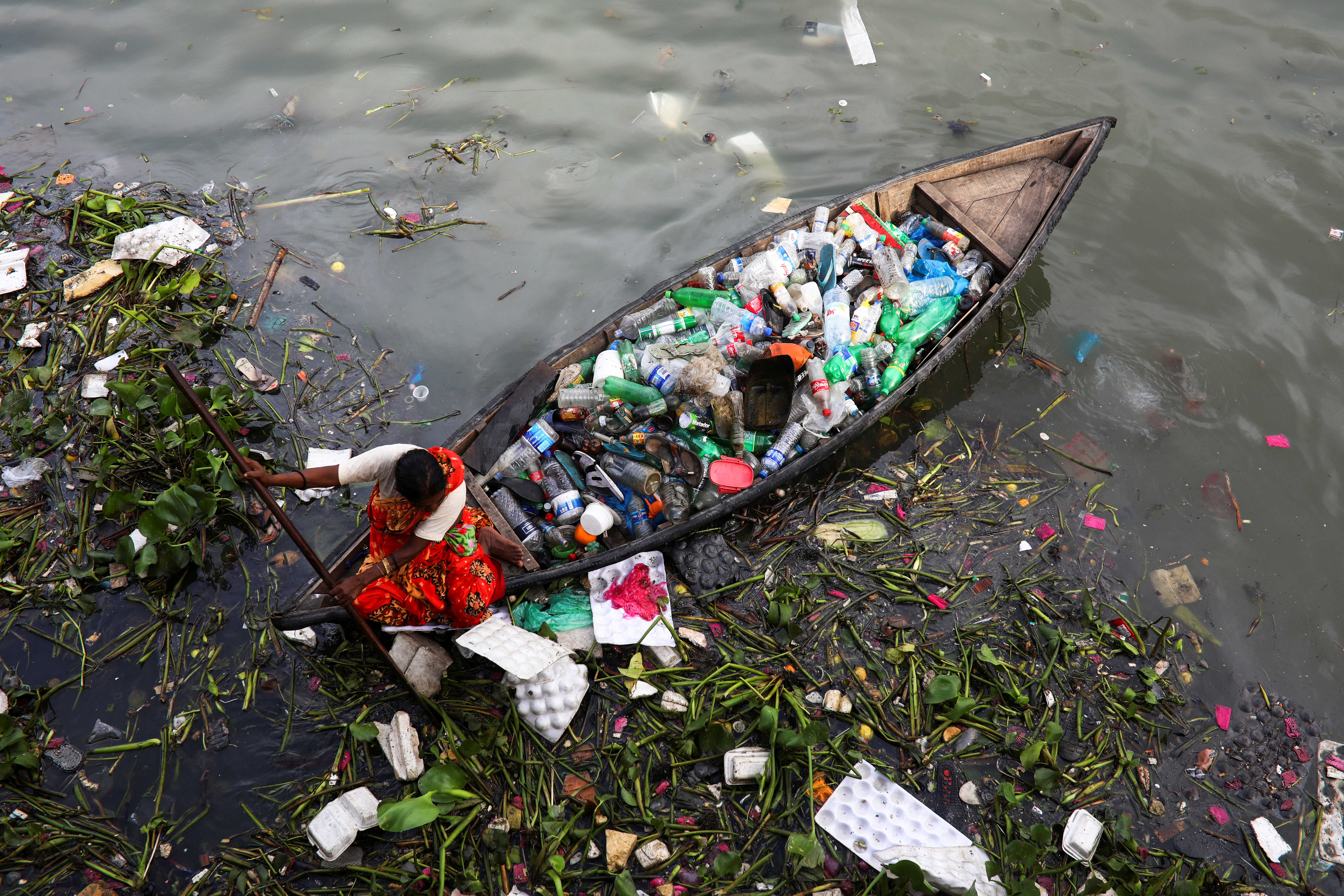 A woman collects plastic waste from the Buriganga river in Dhaka, Bangladesh, September 16, 2020. REUTERS/Mohammad Ponir Hossain     TPX IMAGES OF THE DAY - RC2NZI9KU4BA
