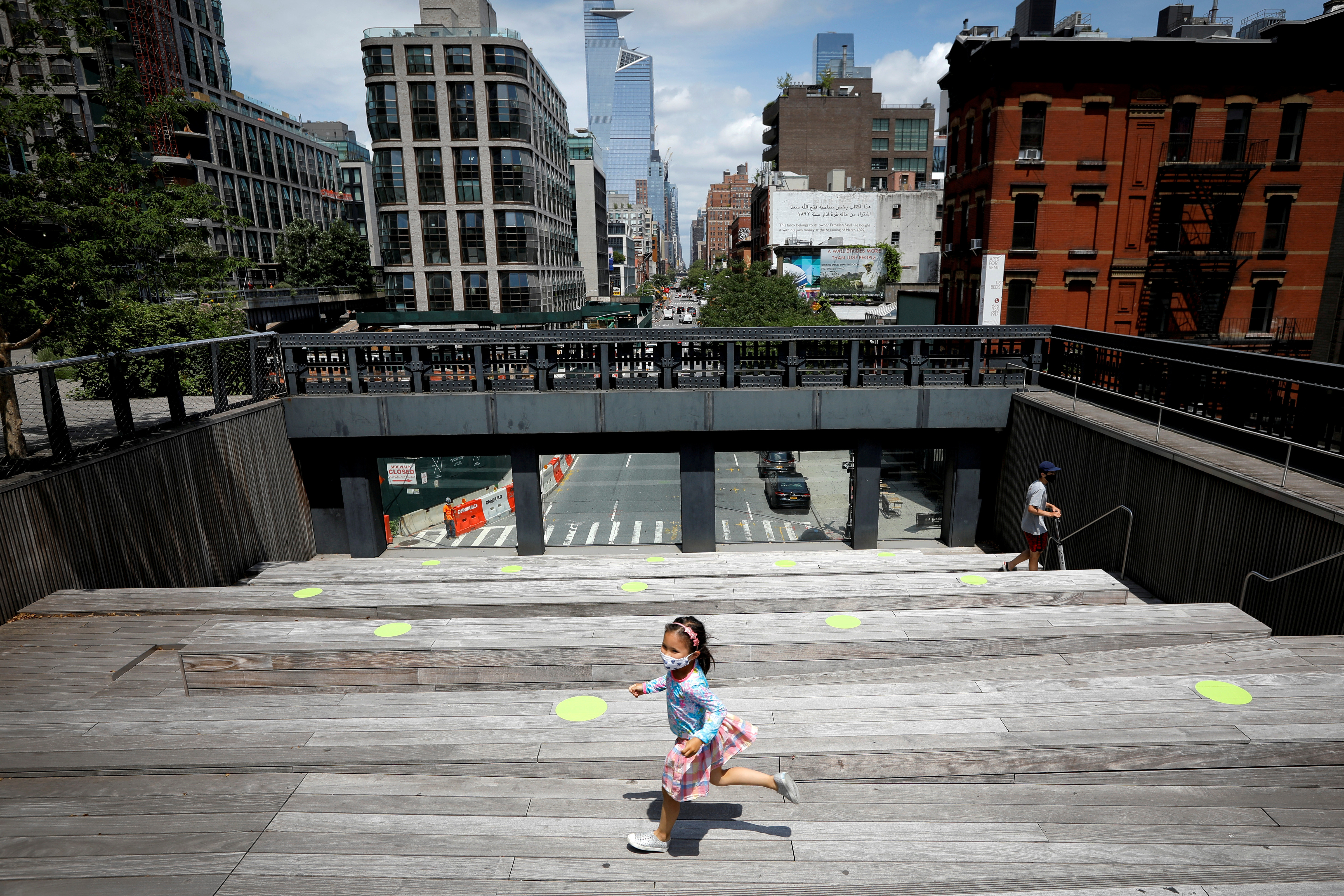 A child wearing a protective face mask plays on a sitting platform painted with social distancing circles on the elevated High Line Park in Manhattan on the first day of the park's re-opening following the outbreak of the coronavirus disease (COVID-19) in New York City, New York, U.S., July 16, 2020. REUTERS/Mike Segar     TPX IMAGES OF THE DAY - RC2IUH9RCCYO