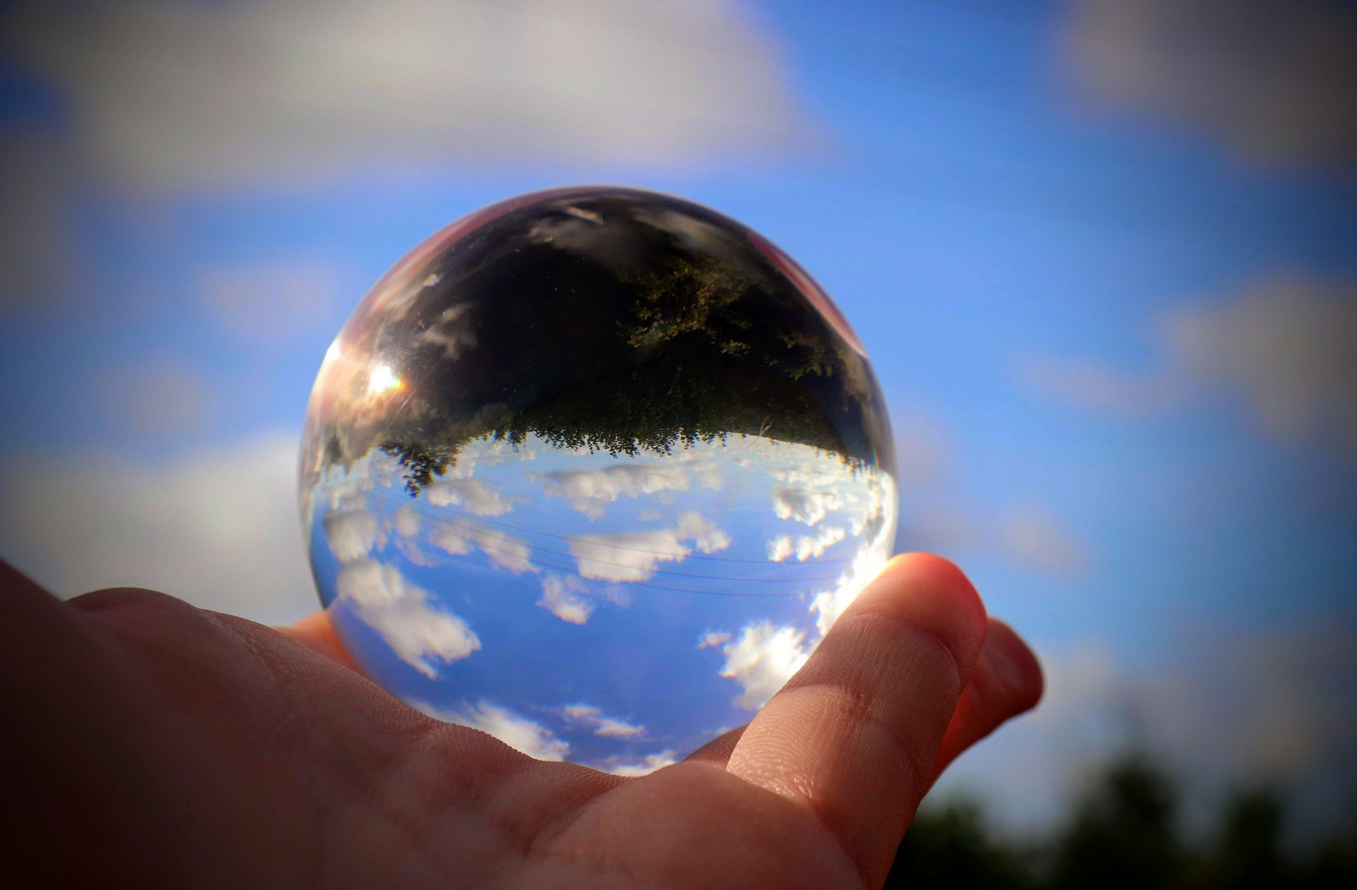 Hand holding glass sphere reflecting sky and earth