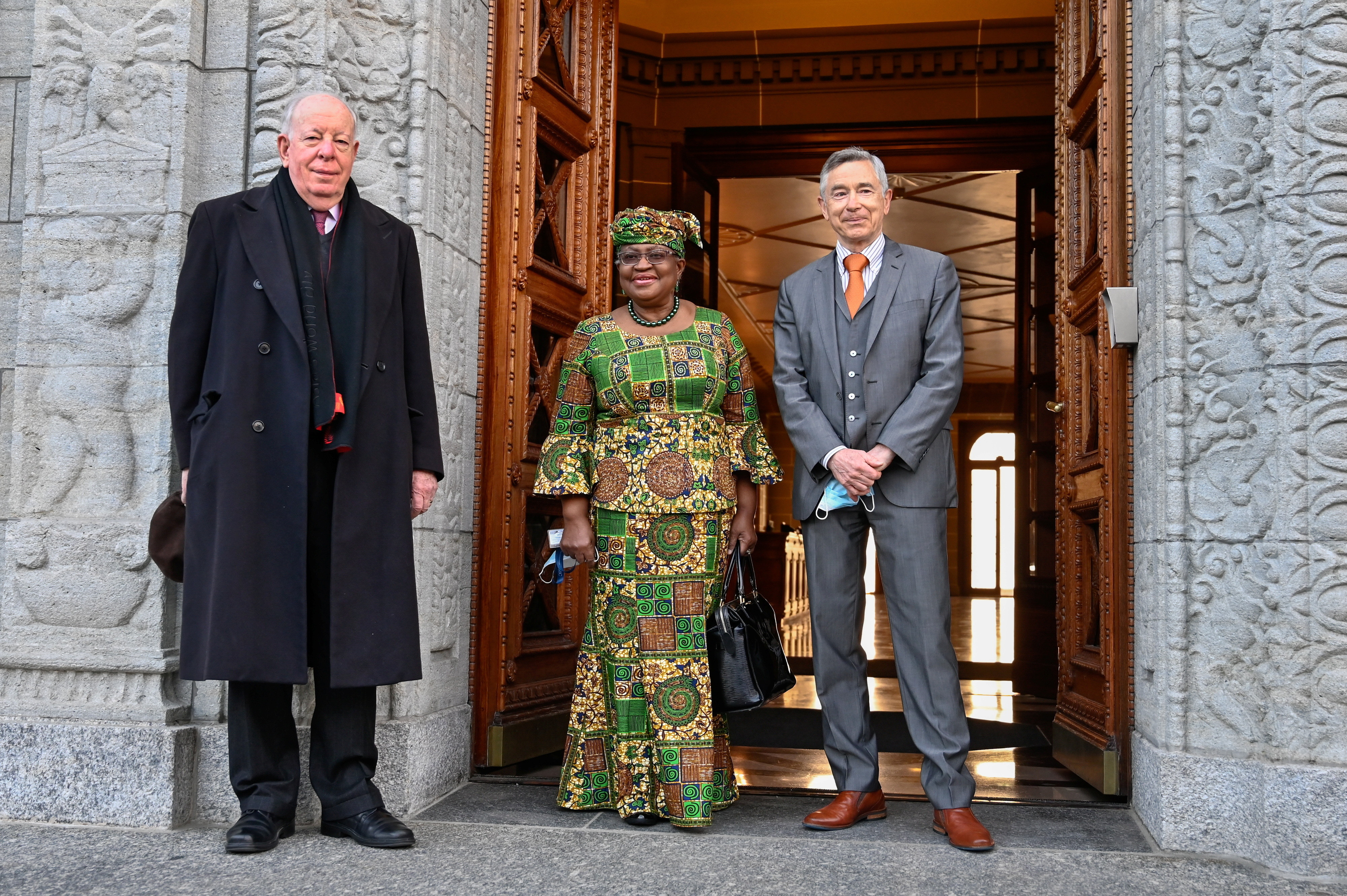 image of new Director-General of the World Trade Organization Ngozi Okonjo-Iweala poses between WTO Deputy Directors-General Alan Wolff (L) and Karl Brauner upon her arrival at the WTO headquarters to take an office in Geneva, Switzerland