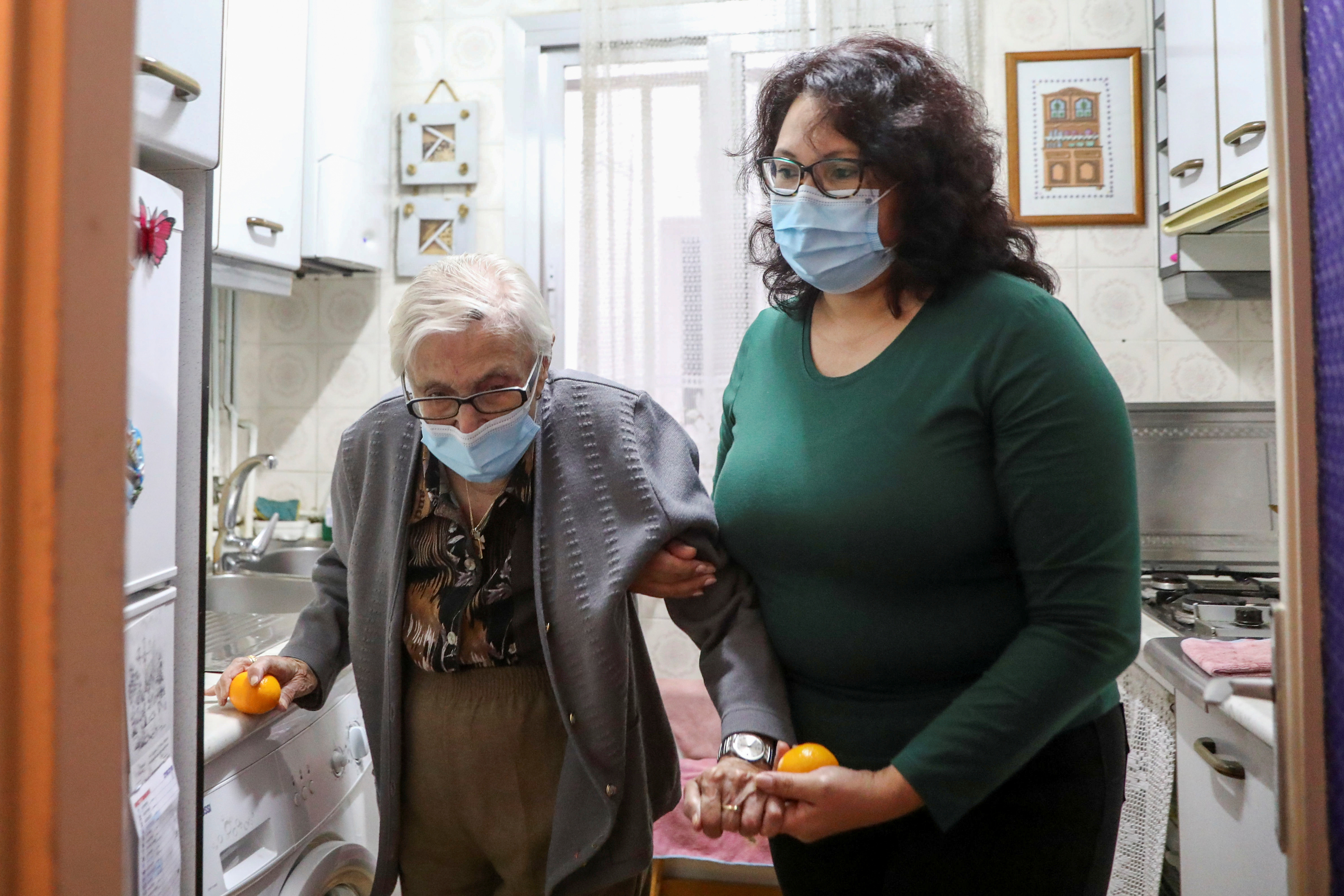 Florentina Martin, a 99 year-old woman who survived coronavirus disease (COVID-19), is helped by her caregiver Olga Arauz in her home in Pinto, near Madrid, Spain, October 20, 2020. Picture taken October 20, 2020. REUTERS/Sergio Perez - RC20NJ9N3H13