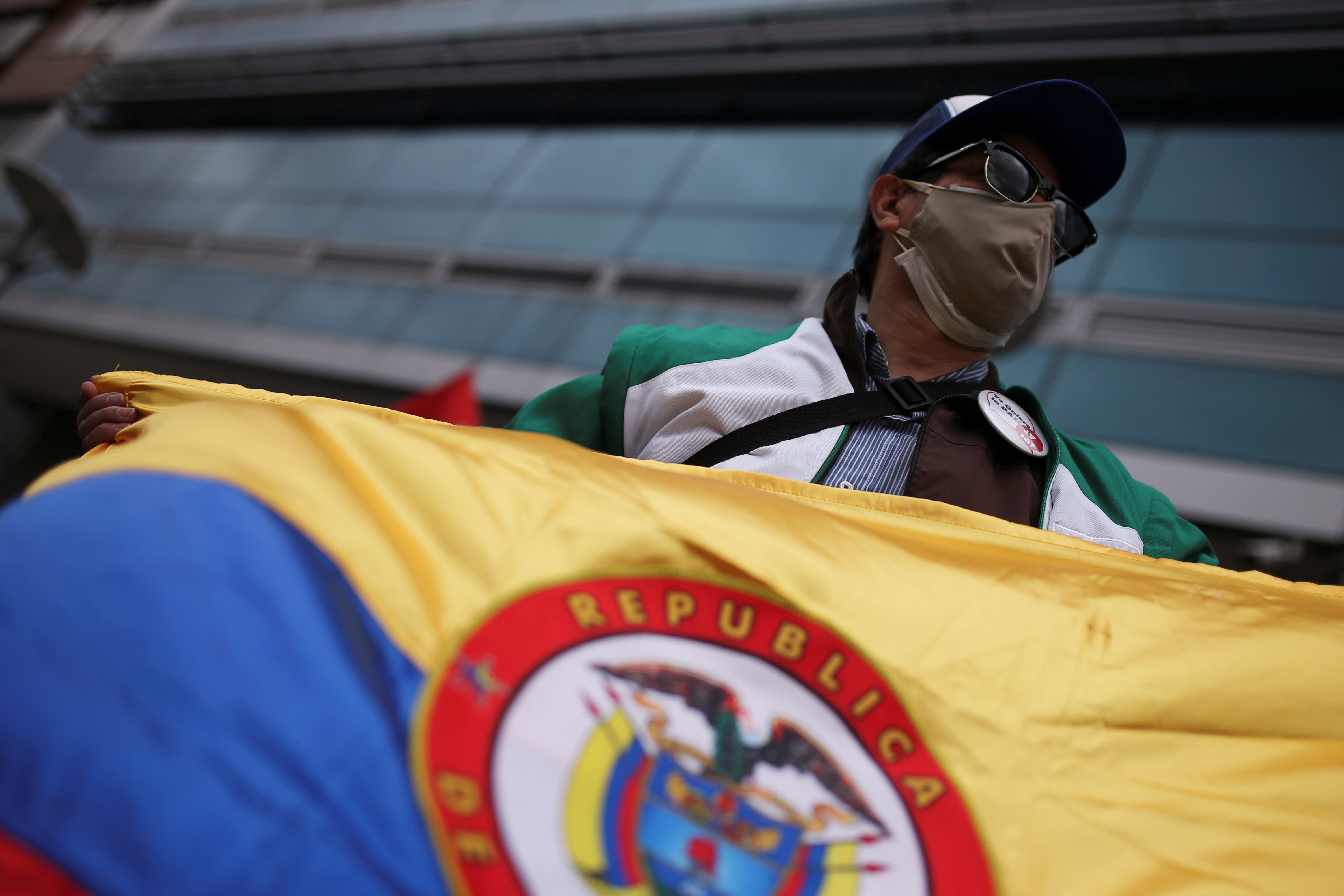 A man wearing a protective mask holds a flag as he protests, amid the coronavirus disease (COVID-19) outbreak, during a national strike, in Bogota, Colombia September 7, 2020.