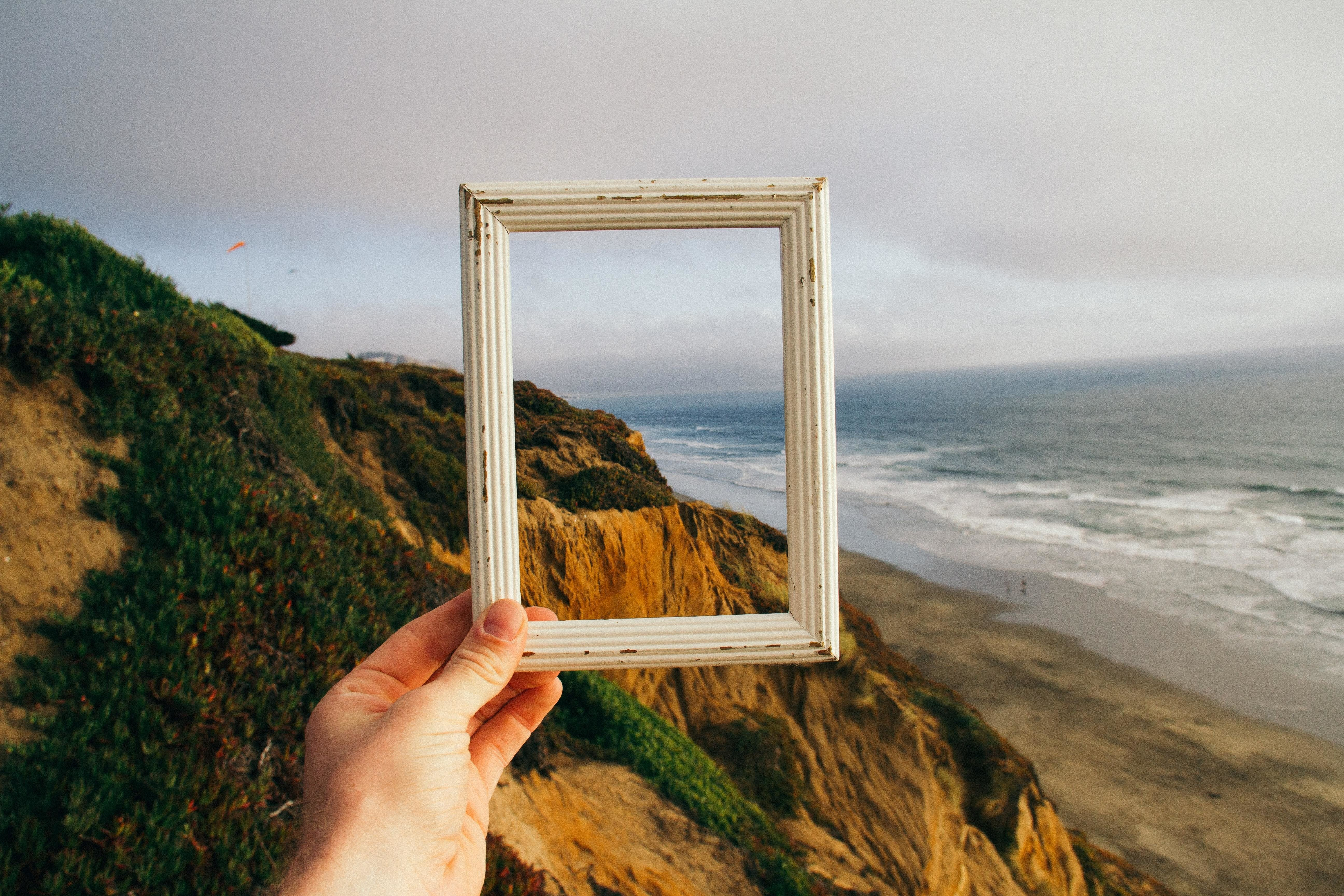Cliffs, beach and sea scene, hand holding white frame; reframing the scene.