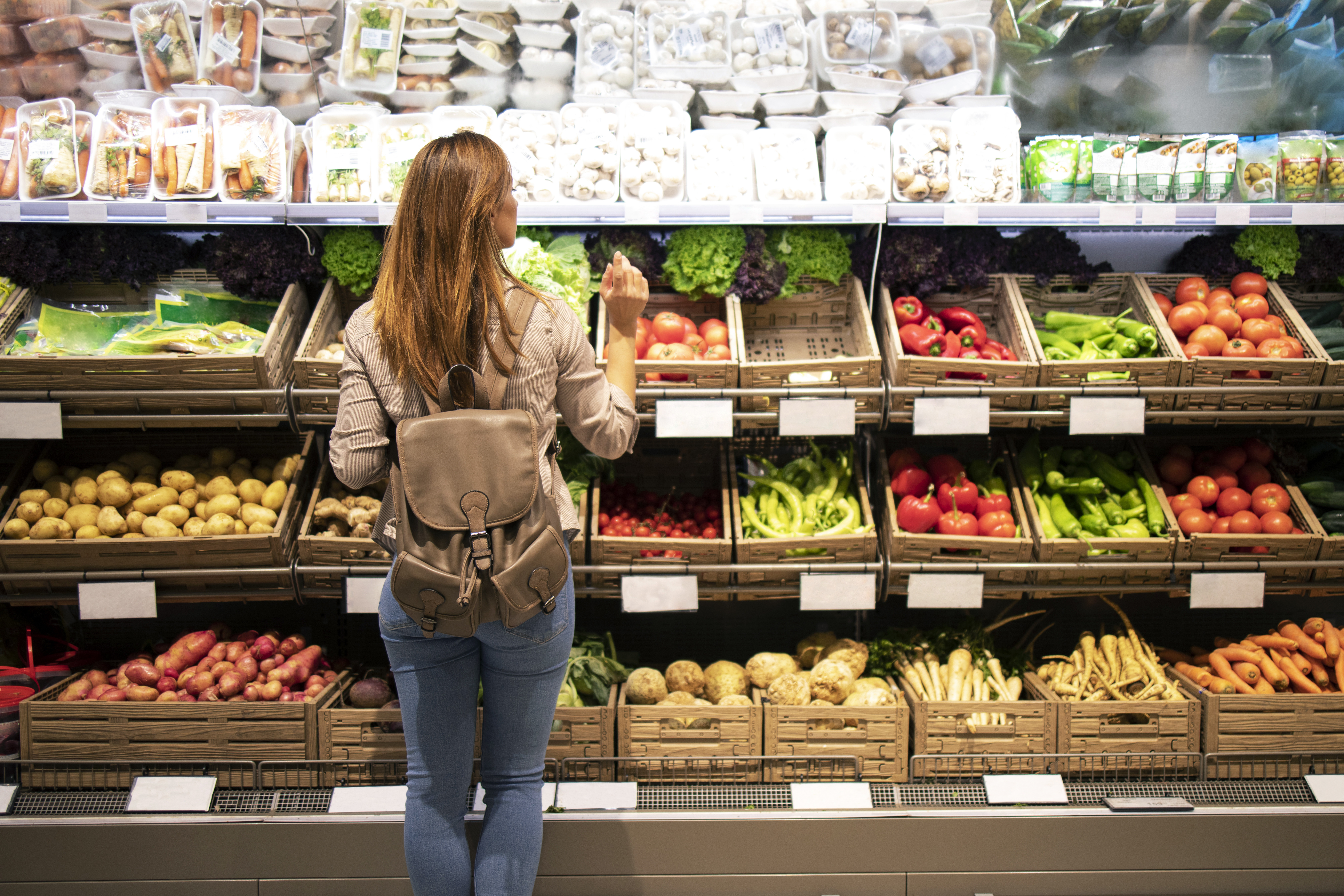 Woman standing in front of vegetable shelves choosing what to buy.