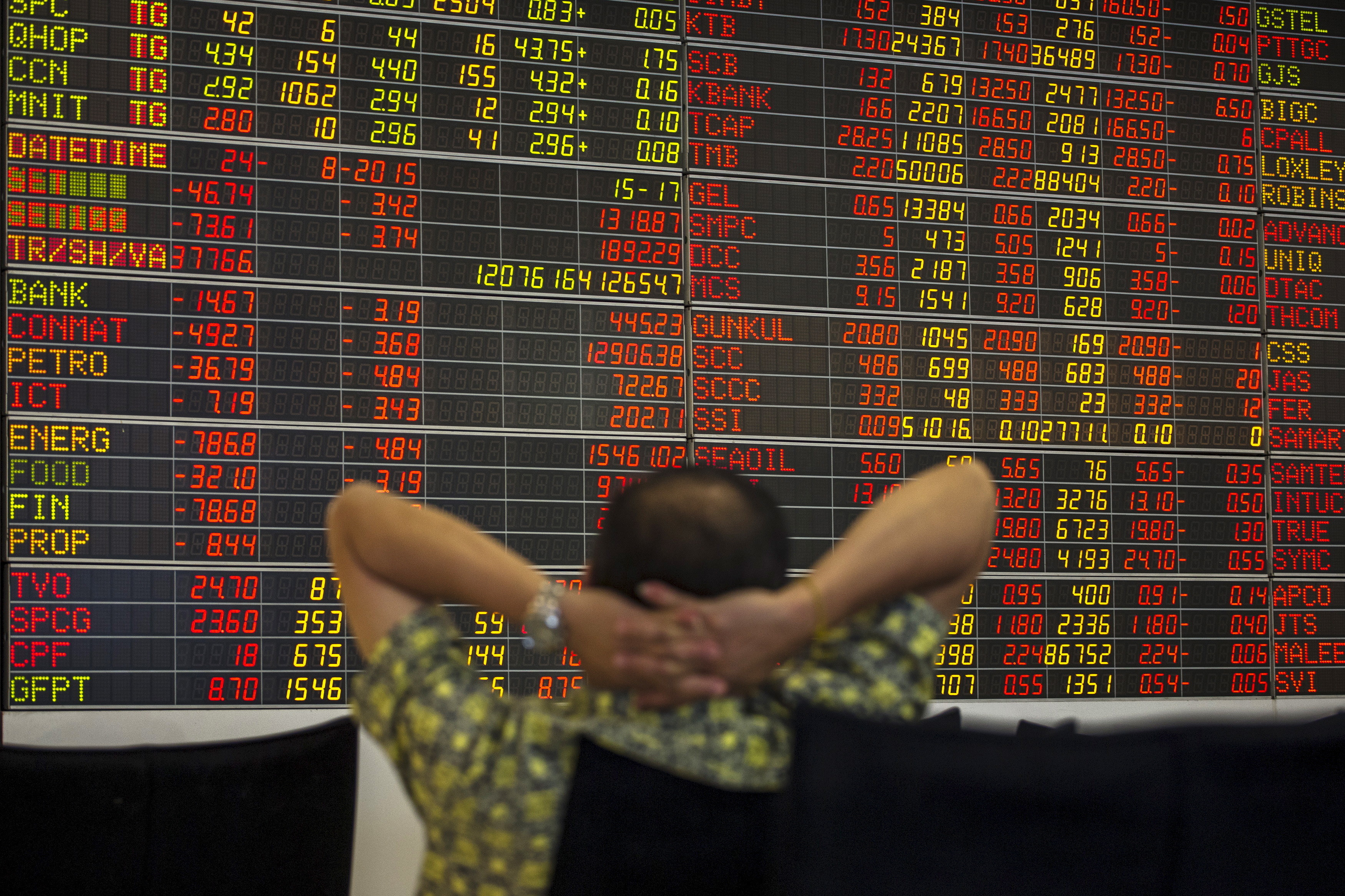 A Thai investor sits in front of an electronic board displaying live market data at a stock broker's office in central Bangkok, Thailand, August 24, 2015. Asian stocks slumped to 3-year lows on Monday as a slide in Chinese equities gathered pace, hastening an exodus from riskier assets as fears of a China-led global economic slowdown churned through markets. REUTERS/Athit Perawongmetha  - GF10000181016
