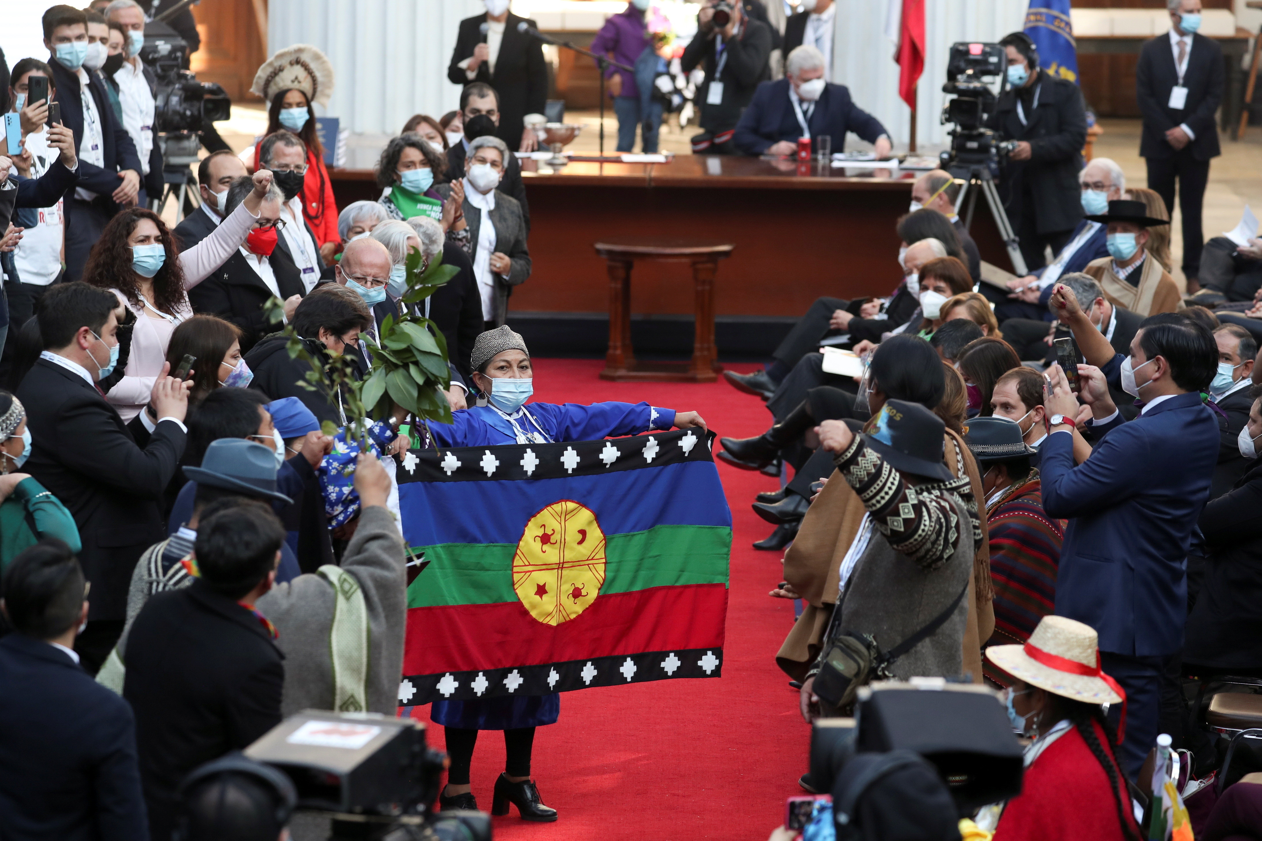 Constitutional assembly president Elisa Loncon holds up a flag as assembly members gather for the first session to draft a new constitution, in Santiago