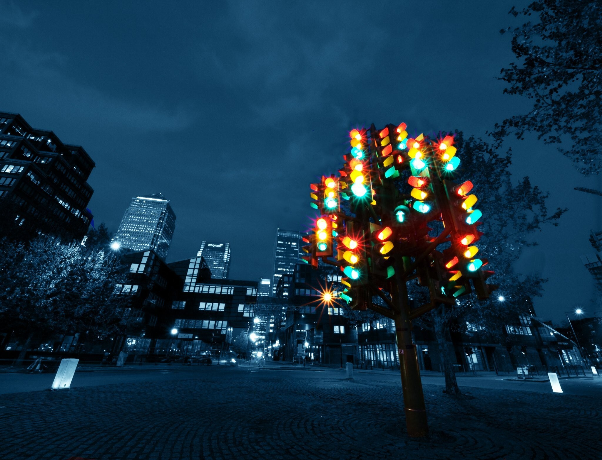 Traffic lights in a tree formation against a city skyline