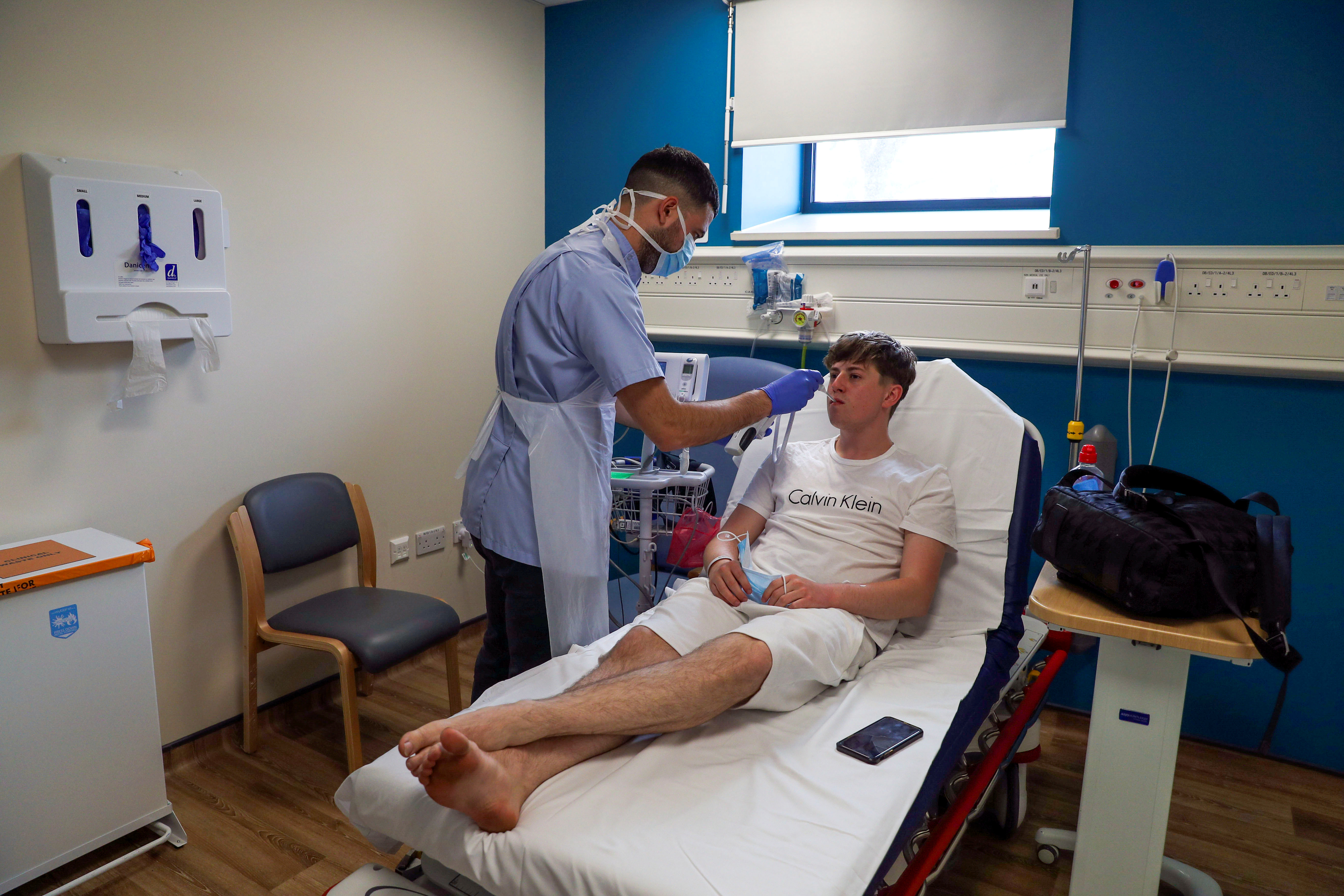 Patient Chay Godfrey is treated by staff nurse Elia Sarno in the Emergency Department at Wexham Park Hospital near Slough, Britain, May 22, 2020. Picture taken May 22, 2020. Steve Parsons/Pool via REUTERS - RC2XWG9NG0V2