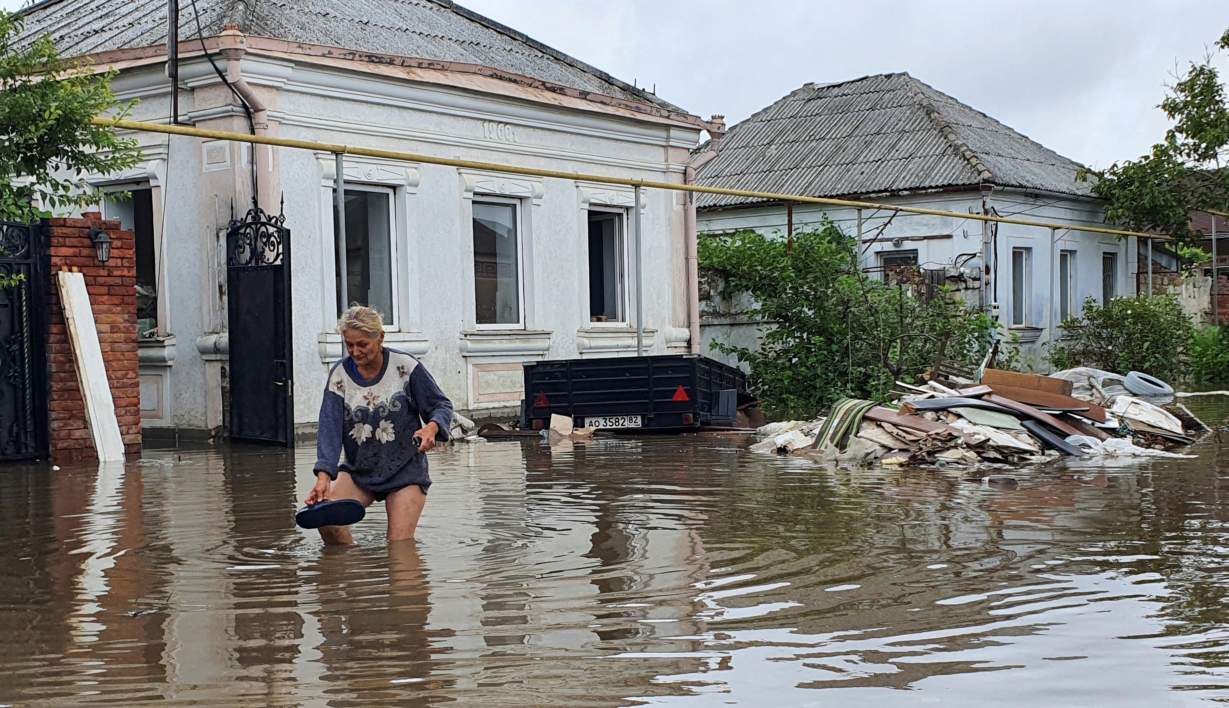 A woman walks along a flooded street following heavy rainfall in Europe.