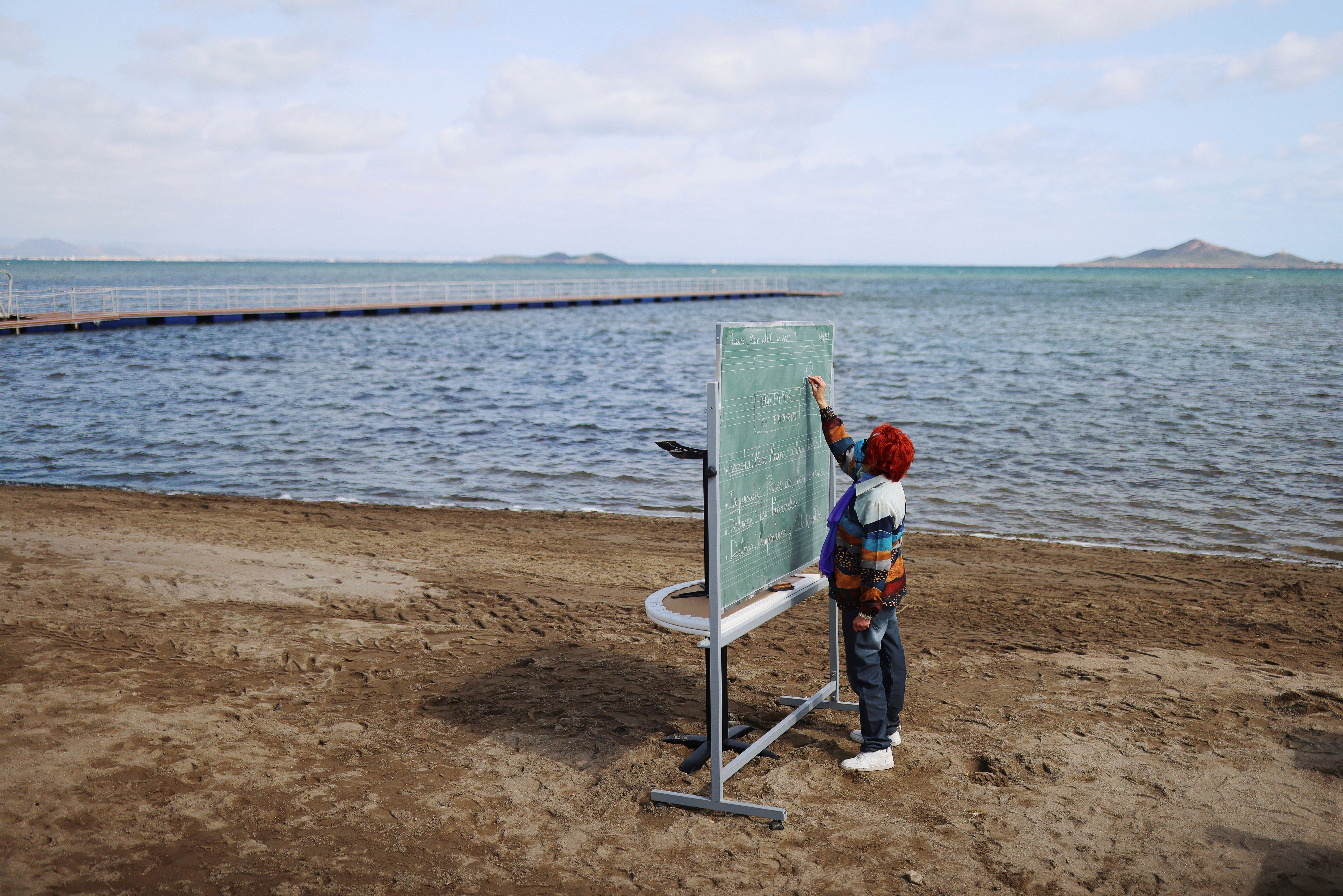 A teacher teaches a class to students (not pictured) of the Felix Rodriguez de la Fuente school, as part of a project known as 'Aire Limpio' (Fresh Air) at the Playa de los Nietos (The Grandchildren's Beach), which aims to use better air quality for children during the coronavirus disease (COVID-19) pandemic, near Cartagena, southern Spain April 8, 2021. Picture taken April 8, 2021. REUTERS/Nacho Doce     TPX IMAGES OF THE DAY - RC29UM9X927W