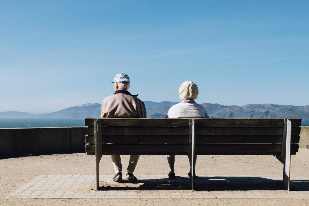 Elderly couple sit on bench.