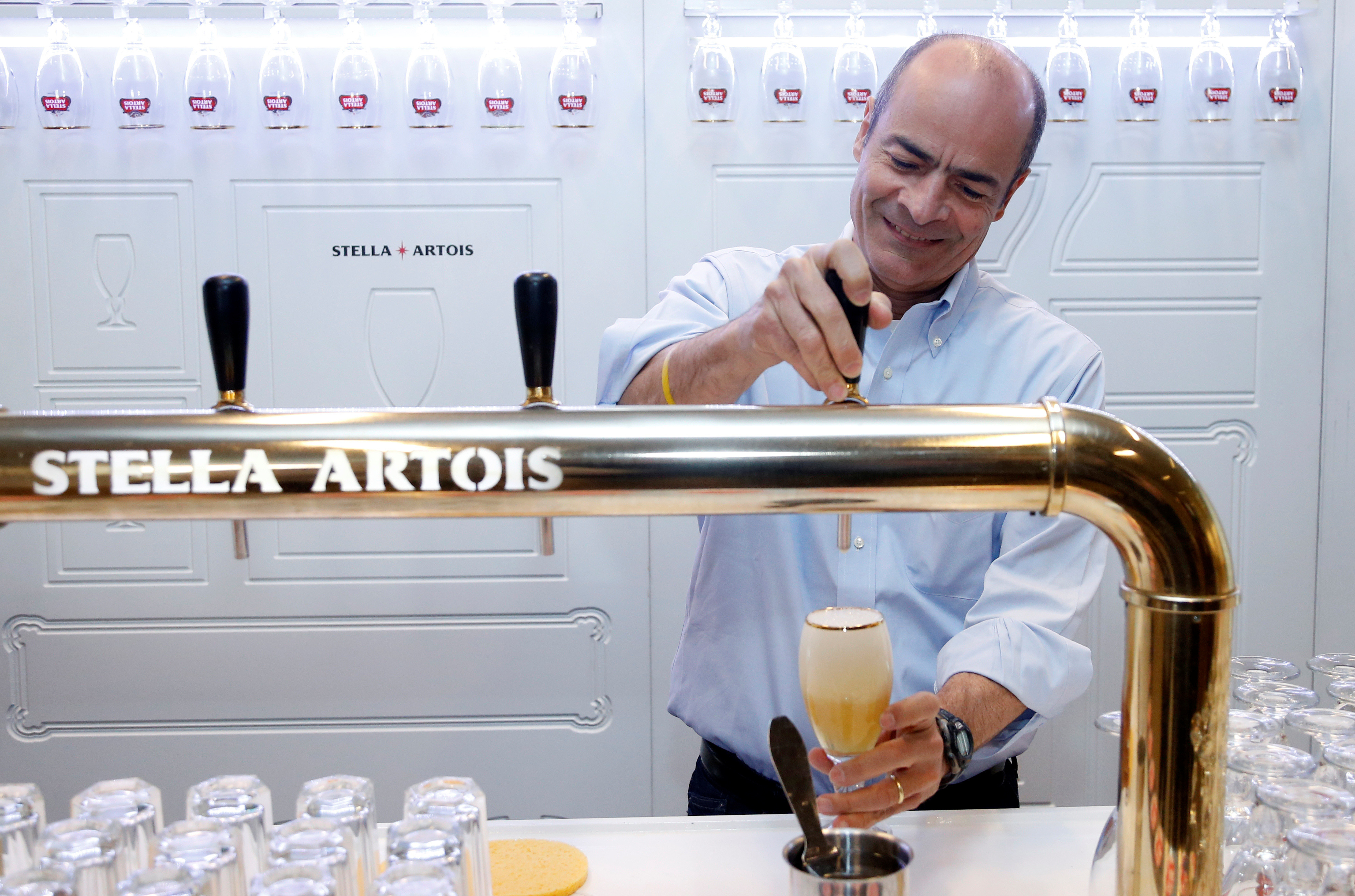 Carlos Brito, Chief Executive of Anheuser-Busch InBev, taps a Stella Artois beer after a news conference in Leuven, Belgium March 1, 2018.
