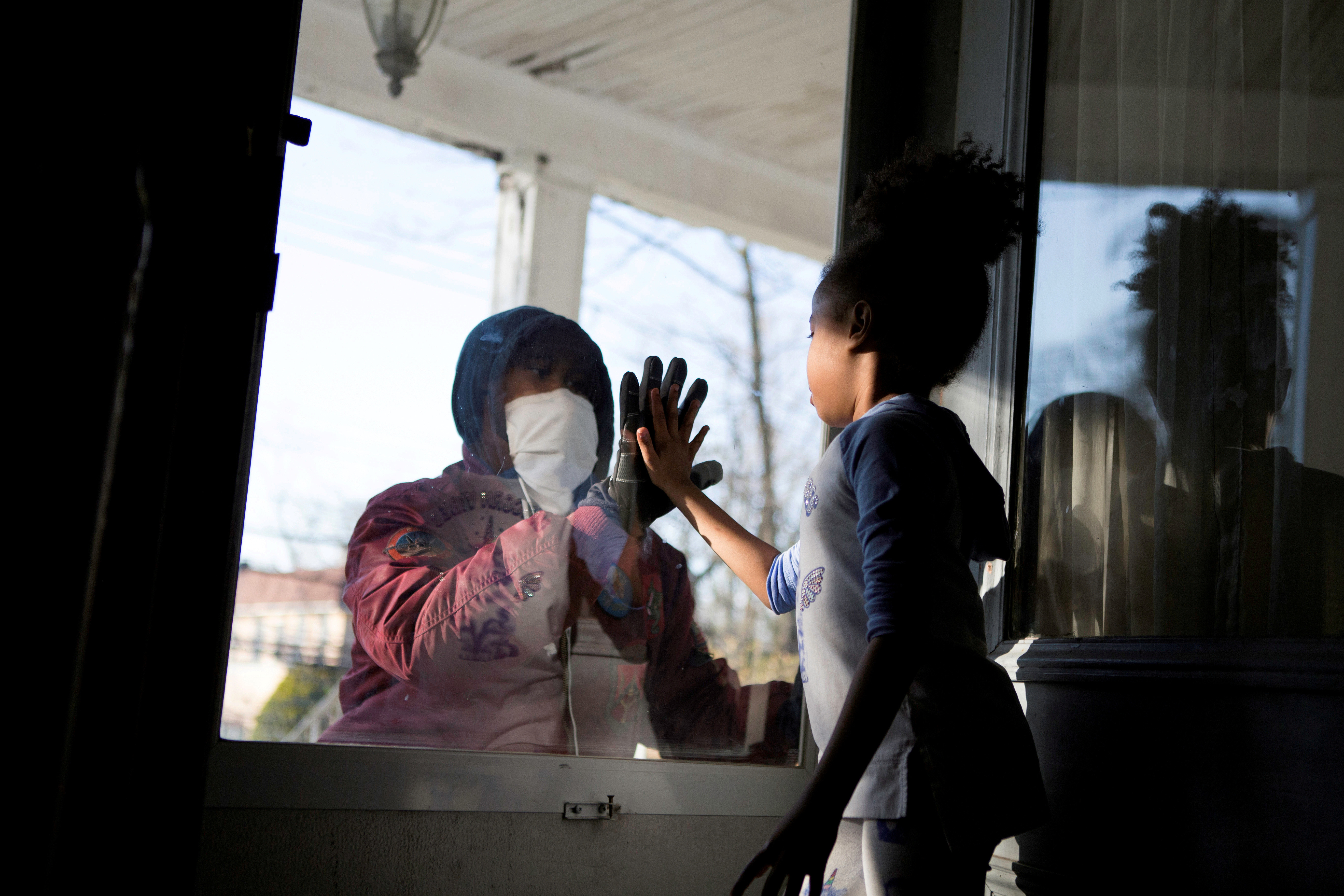 Hashim, an essential worker in the healthcare industry, greets his daughter through the closed door as he maintains social distance from his family as he works amid the coronavirus disease (COVID-19) outbreak in New Rochelle, New York, U.S., April 11, 2020. Picture taken April 11, 2020.  REUTERS/Joy Malone     TPX IMAGES OF THE DAY  REFILE - CORRECTING STATE - RC253G9I4I5B