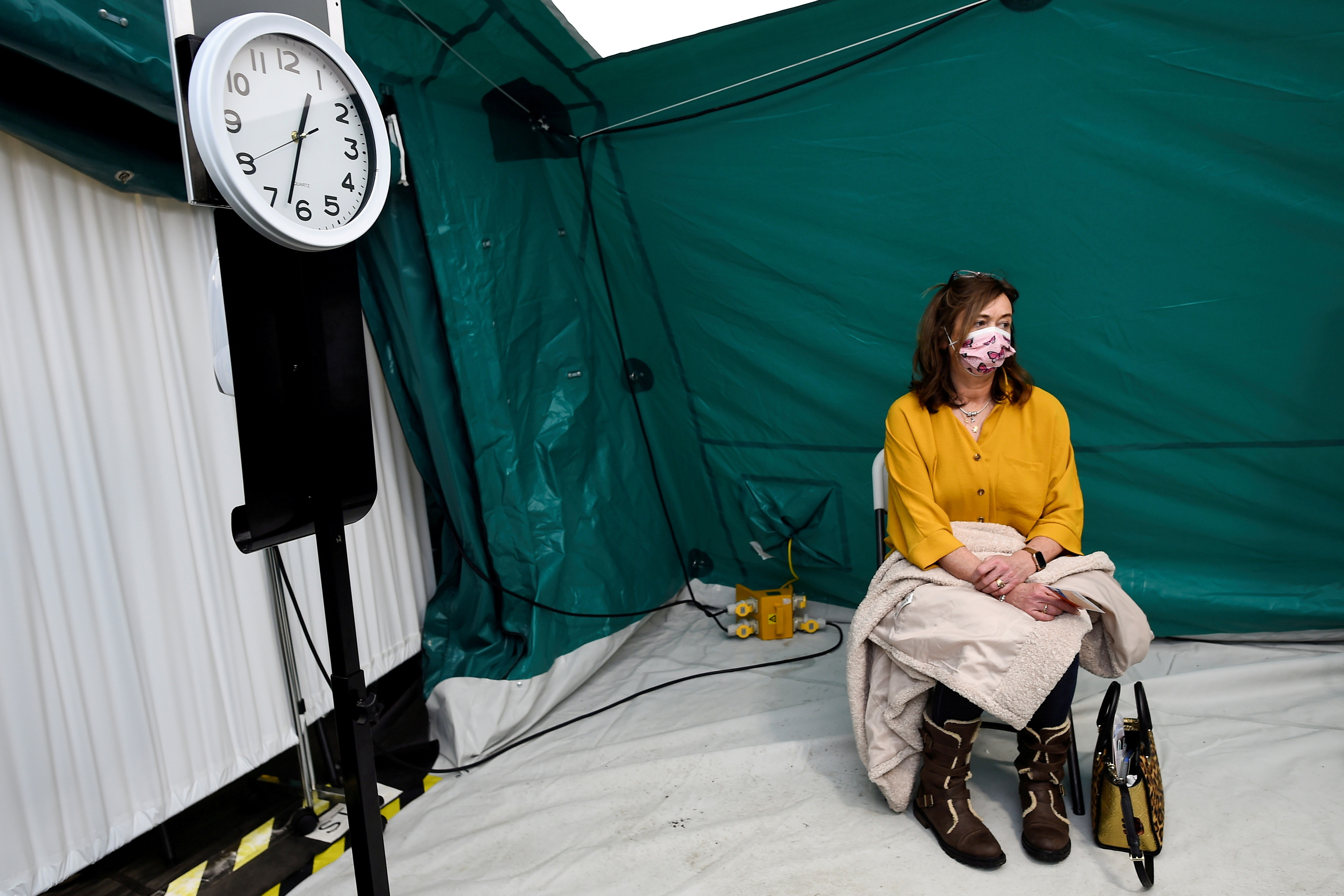 Margaret Kyne Delaney sits in an observation area after receiving AstraZeneca coronavirus disease (COVID-19) vaccine at an HSE (Health Service Executive) vaccination centre outside St. Mary's Hospital, in Phoenix Park in Dublin, Ireland, February 14, 2021.  REUTERS/Clodagh Kilcoyne     TPX IMAGES OF THE DAY - RC2DSL9OY7UU