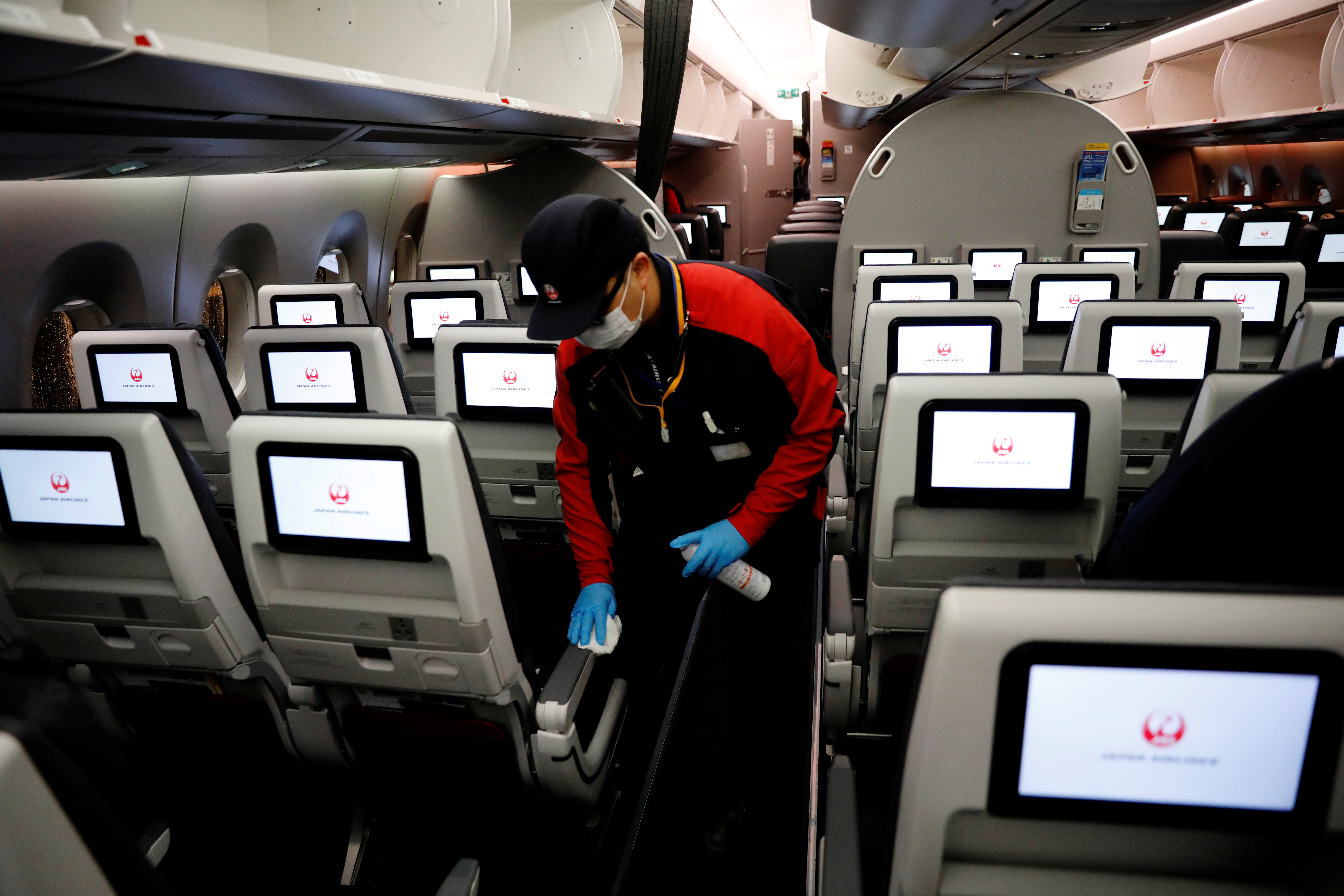 A staff member of Japan Airlines wearing a protective face mask and gloves cleans the cabin of a plane which performed a domestic flight, amid the coronavirus disease (COVID-19) outbreak at Haneda airport in Tokyo, Japan May 26, 2020. Picture taken May 26, 2020. REUTERS/Kim Kyung-Hoon - RC262H9ILONT
