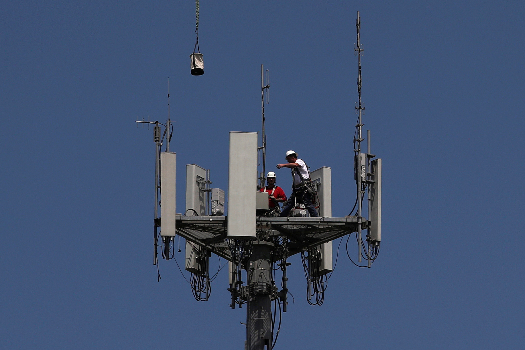 Workers install 5G telecommunications equipment on a T-Mobile US Inc tower in Seabrook, Texas, U.S. May 6, 2020.