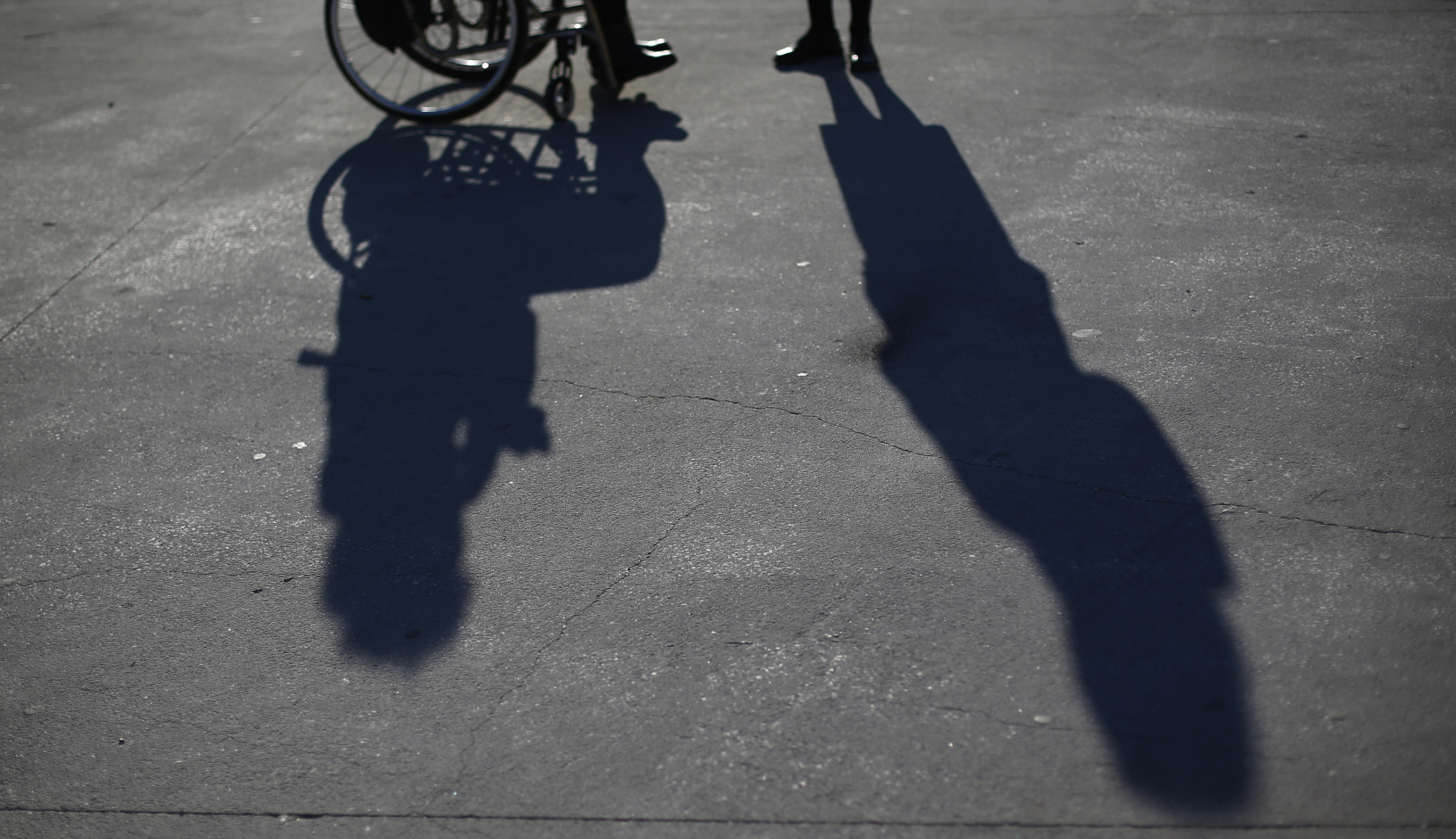 a shadow of a wheelchair user on the pavement