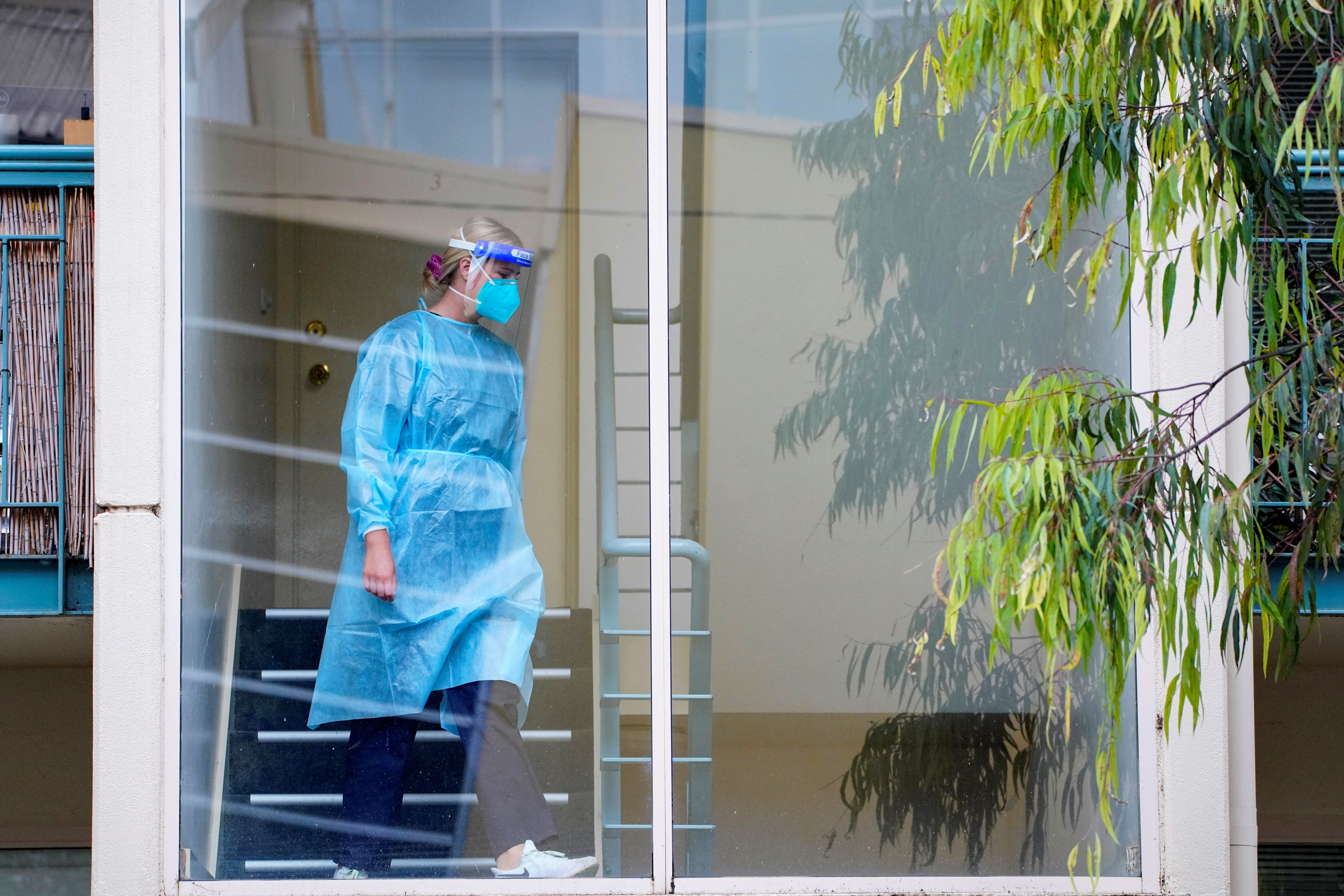 A healthcare worker walks down stairs at the Kings Park townhouse complex locked down in response to an outbreak of the coronavirus disease (COVID-19), in Melbourne, Australia, June 16, 2021.  REUTERS/Sandra Sanders - RC2D1O9WK3JD