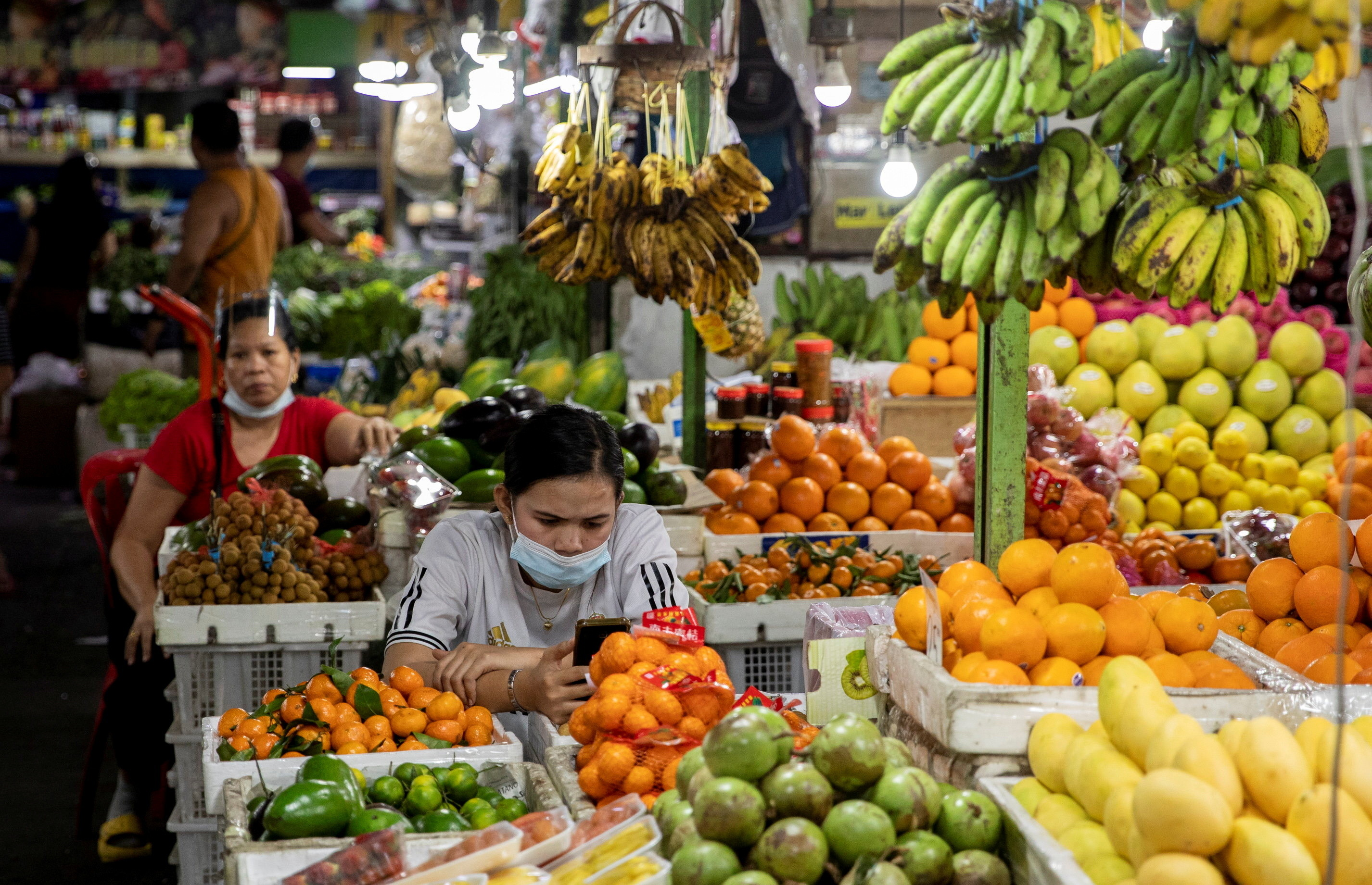 a picture of fruit sellers surrounded by different coloured fruits