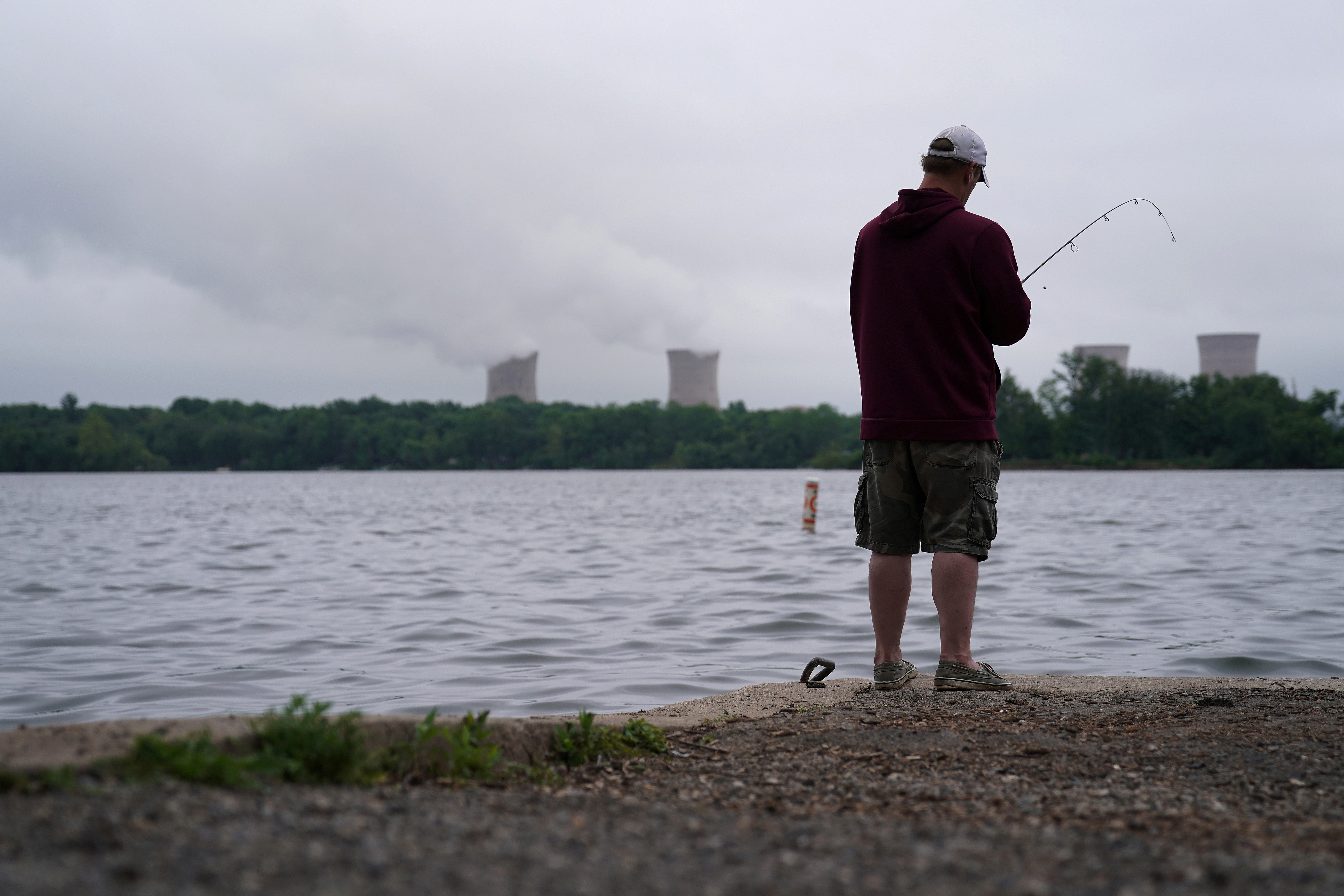 A man fishes in the Susquehanna River in front of the Three Mile Island Nuclear power plant in Goldsboro, Pennsylvania, U.S. May 30, 2017. REUTERS/Carlo Allegri - RC1670FDEB70
