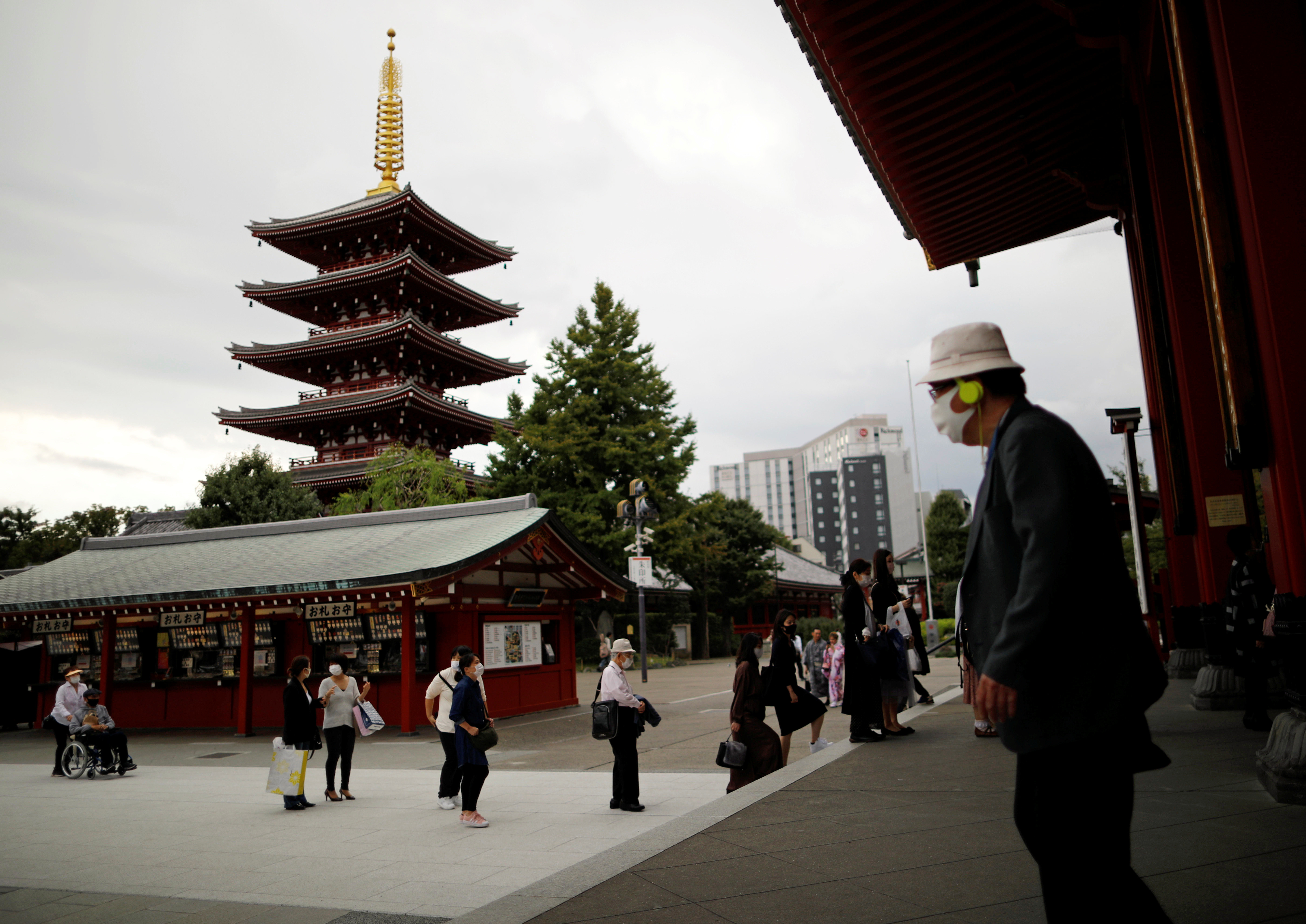 Visitors wearing protective face masks practice social distancing as they offer prayers at a temple at Asakusa district, a popular sightseeing spot, amid the coronavirus disease (COVID-19) outbreak in Tokyo, Japan October 13, 2020.   REUTERS/Issei Kato - RC2KHJ9ZNXUP