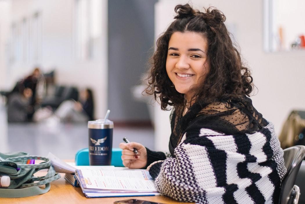 Girl sits at desk doing work at university.