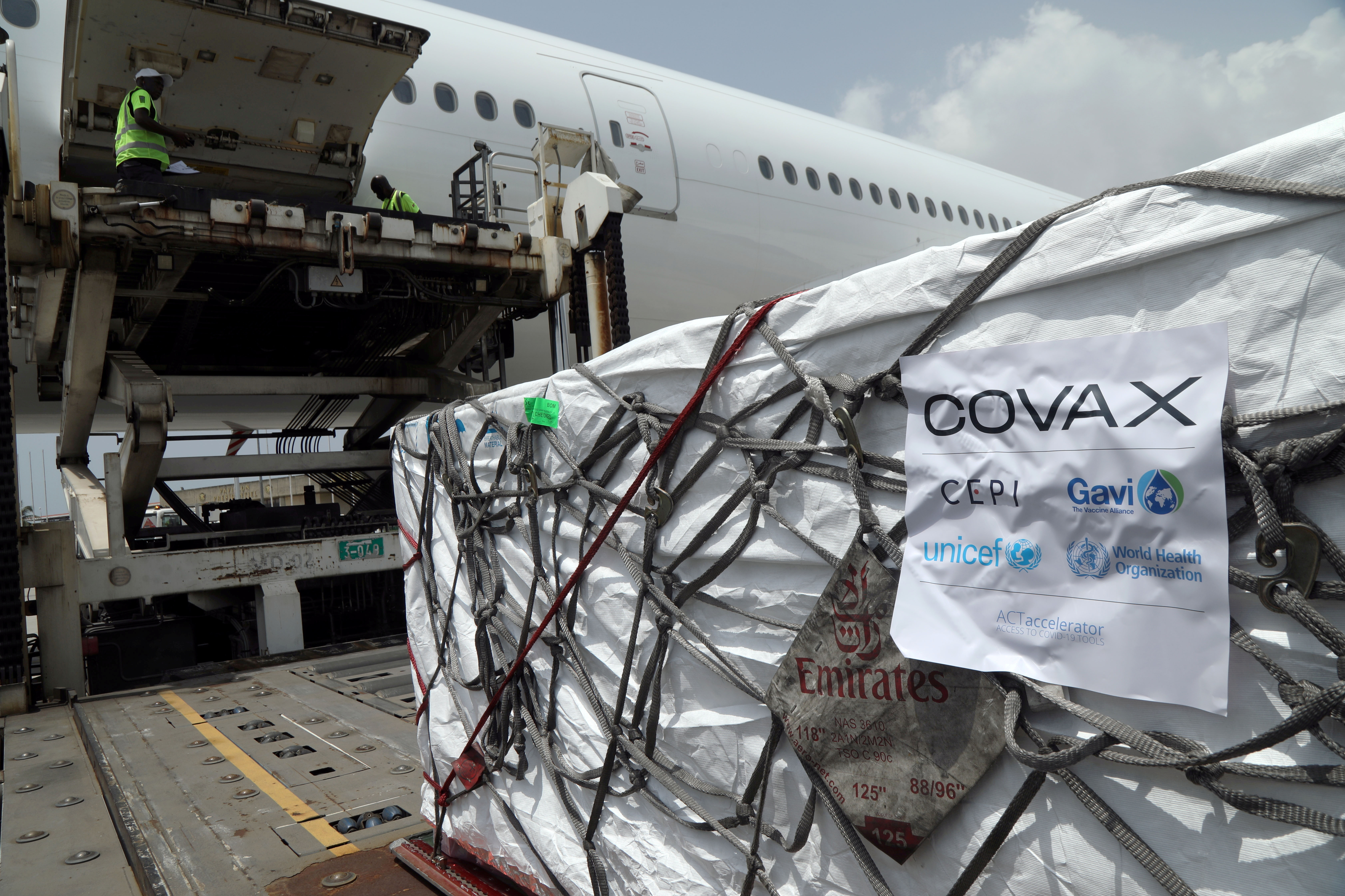 Workers offload boxes of AstraZeneca/Oxford vaccines as the country receives its first batch of coronavirus disease (COVID-19) vaccines under COVAX scheme, in Abidjan, Ivory Coast February 26, 2021. REUTERS/Luc Gnago - RC2C0M9YAB90