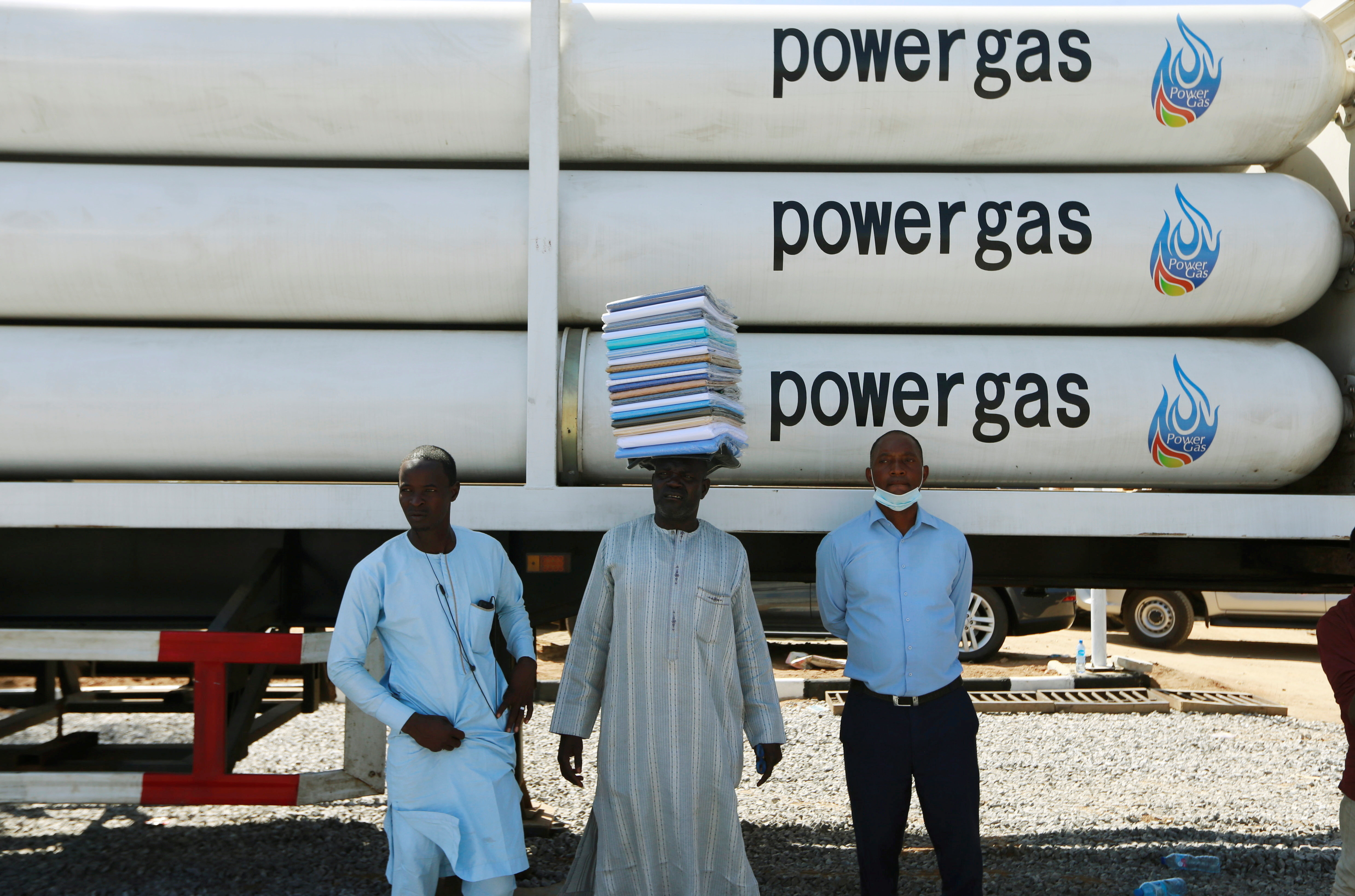 Men stand near a gas truck during the unveiling of the National Gas Expansion Programme, in Abuja, Nigeria.