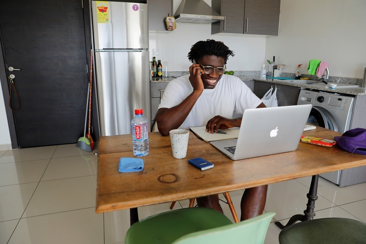 Jeff Provencal, 33, works from home after being released from a 14-day quarantine, as Ghana enforces a partial lockdown in the cities of Accra and Kumasi to slow the spread of the coronavirus disease (COVID-19), Accra, Ghana April 6, 2020. REUTERS/Francis Kokoroko - RC24ZF91G5SA