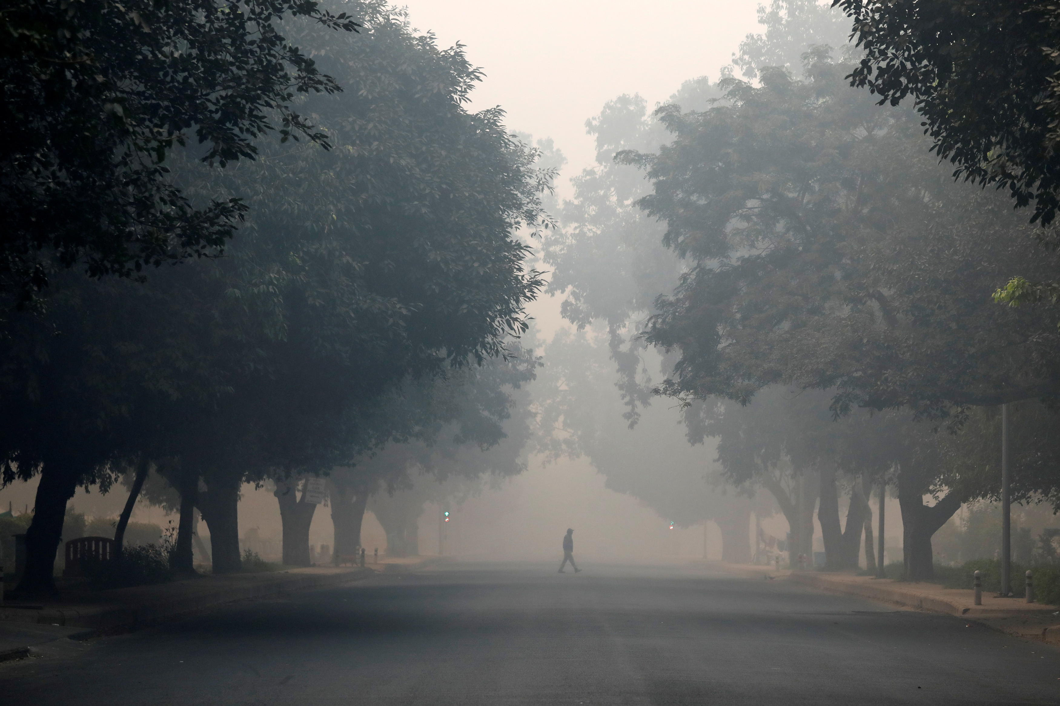 A man crosses a road on a smoggy morning in New Delhi, India, November 8, 2018