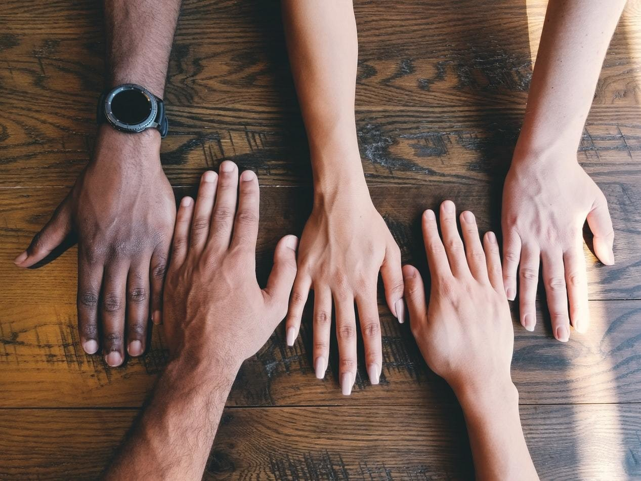5 hands, of different genders and skin tones.
