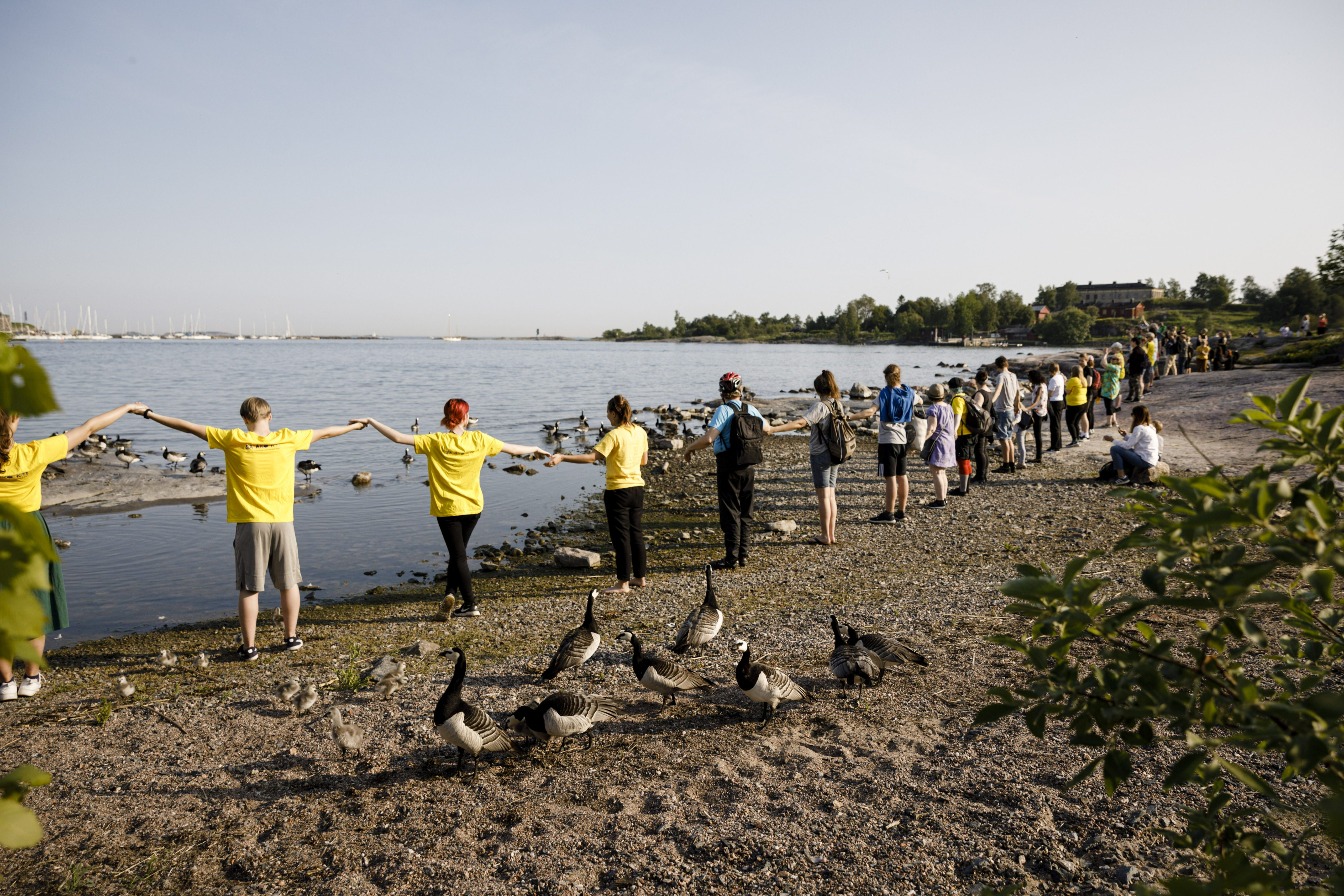 People clean the Baltic Sea coastline during the World Environment Day Clean-Up event in Kaivopuisto Park in Helsinki, Finland