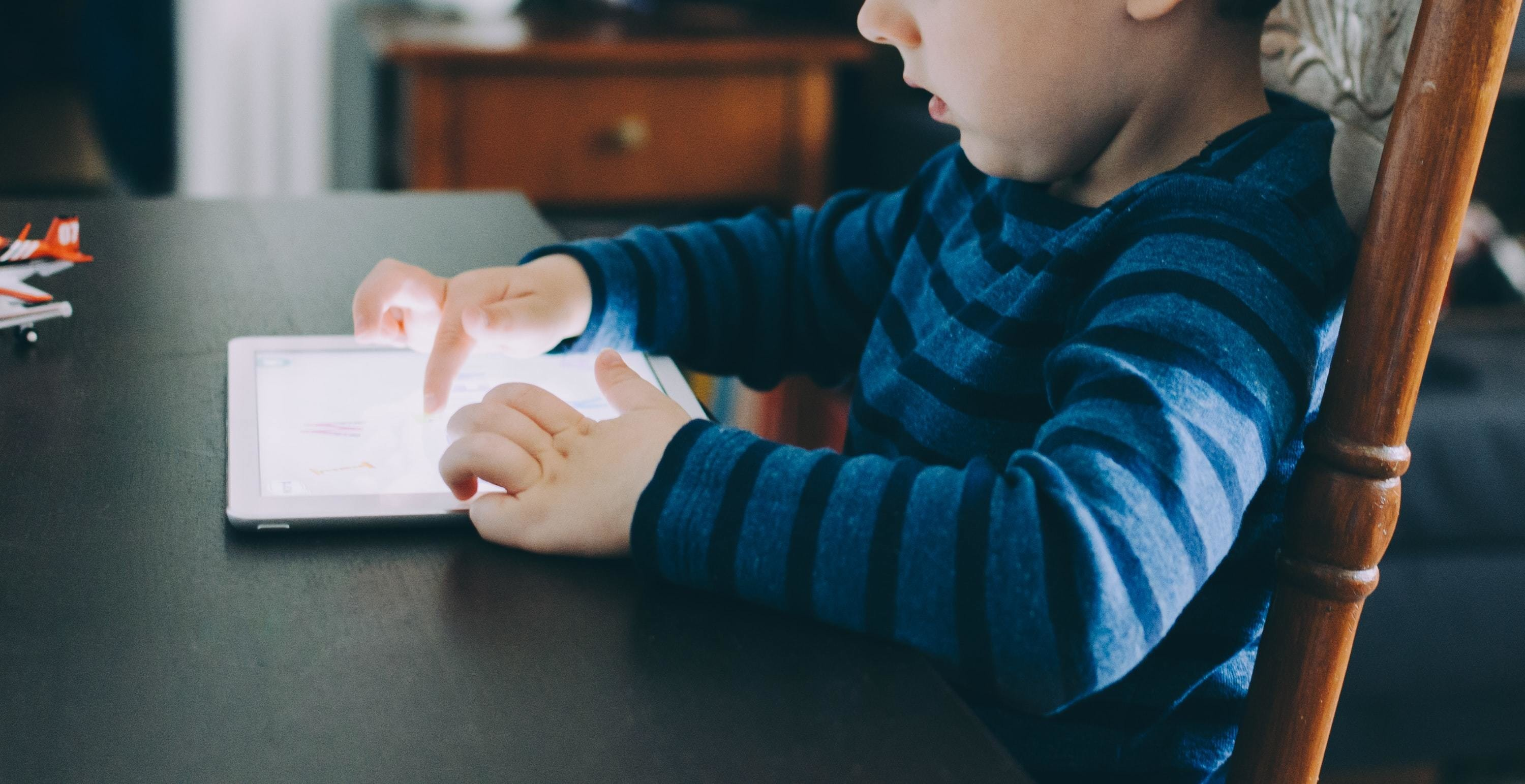 To get the educational benefits from using a tablet, it's best for children to focus on interactive tasks like this young boy is doing here, rather than passive ones.