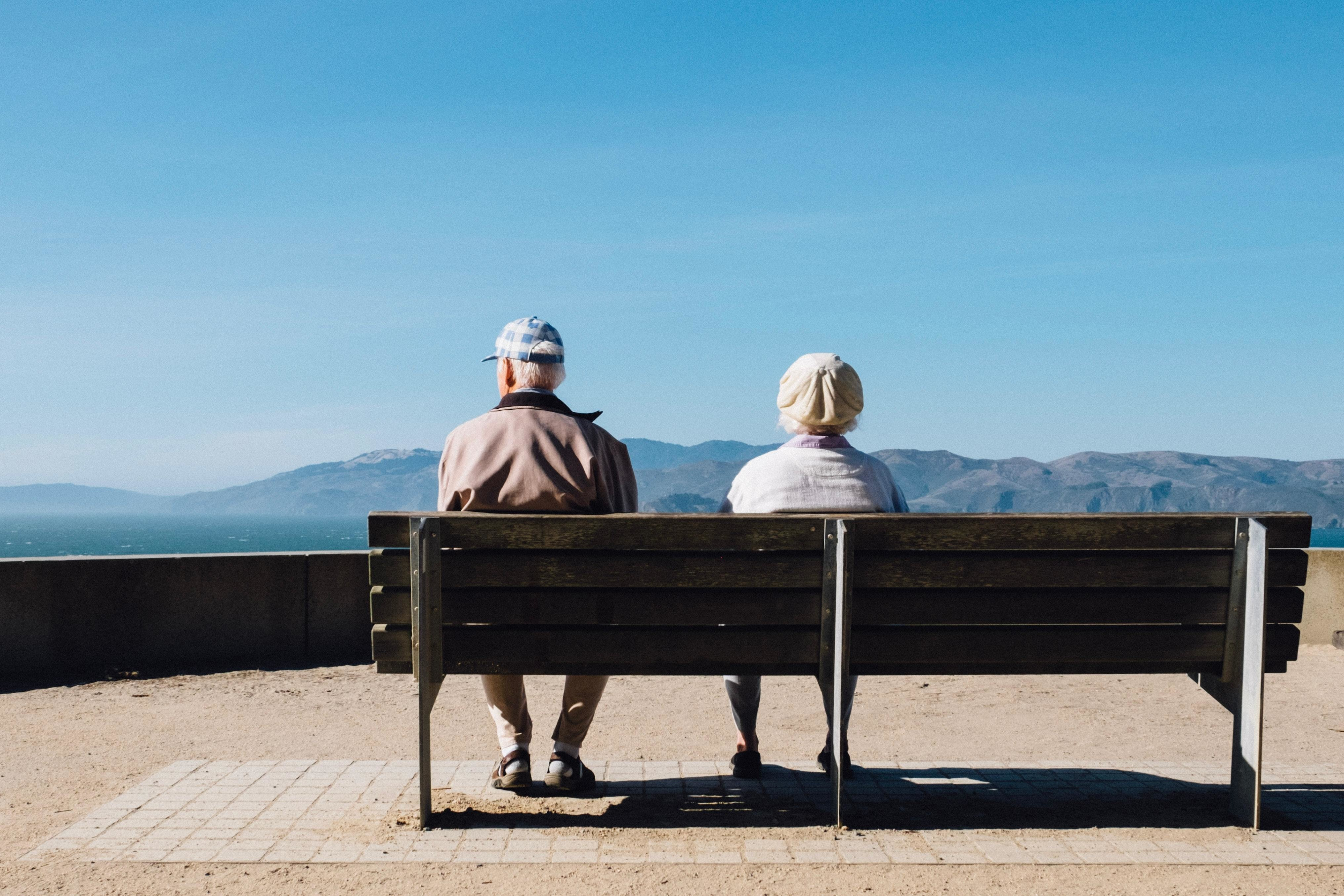 Retired couple sat on a bench looking out to sea.