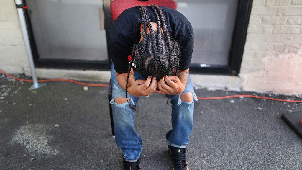 A person bows her head in her hands as she became apprehensive and nervous about being tested for COVID-19