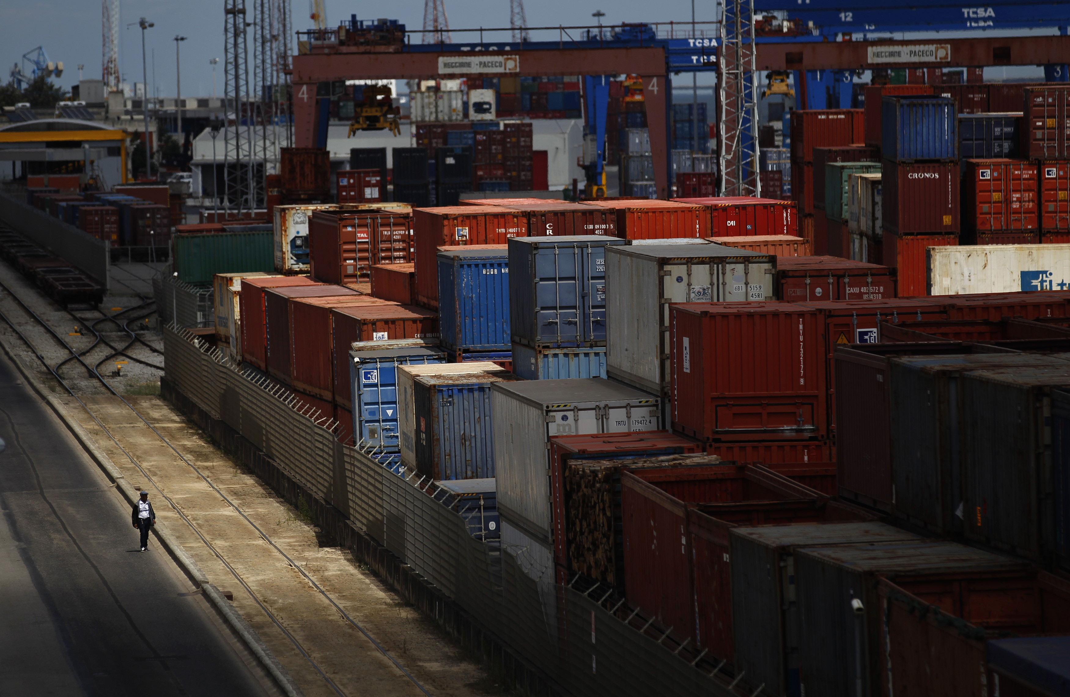 A man walks near containers at a port in Lisbon August 14, 2012. Portuguese port workers started a midnight strike against the revision of the legal framework for dock work.  REUTERS/Rafael Marchante (PORTUGAL - Tags: BUSINESS EMPLOYMENT MARITIME CIVIL UNREST TPX IMAGES OF THE DAY) - GM2E88F00EP01