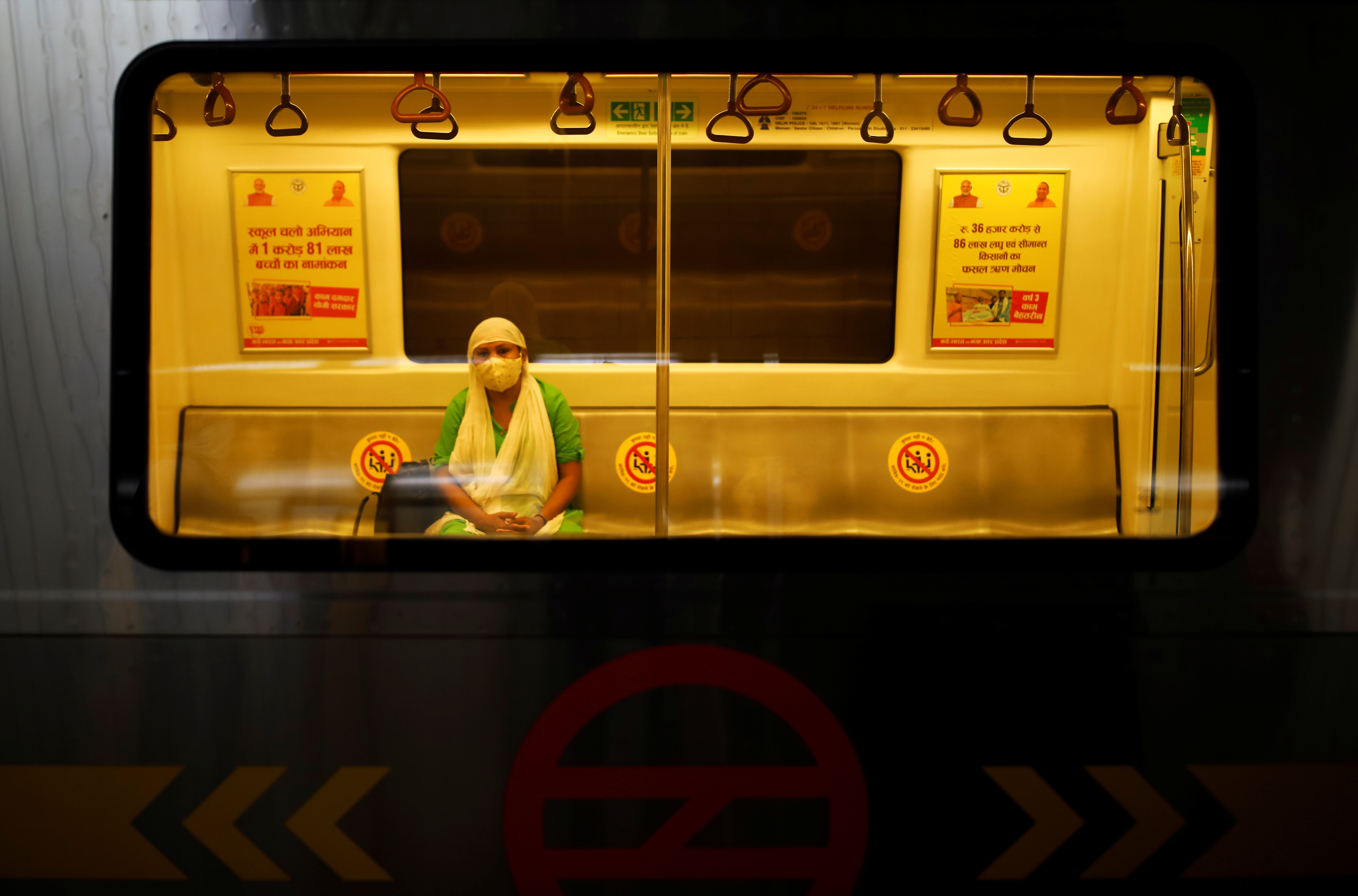 A woman wearing a face mask travels inside a Delhi metro train, on the first day of the restart of their operations, amidst the spread of coronavirus disease (COVID-19), in New Delhi, India, September 7, 2020. REUTERS/Adnan Abidi - RC2ITI9WIHTH