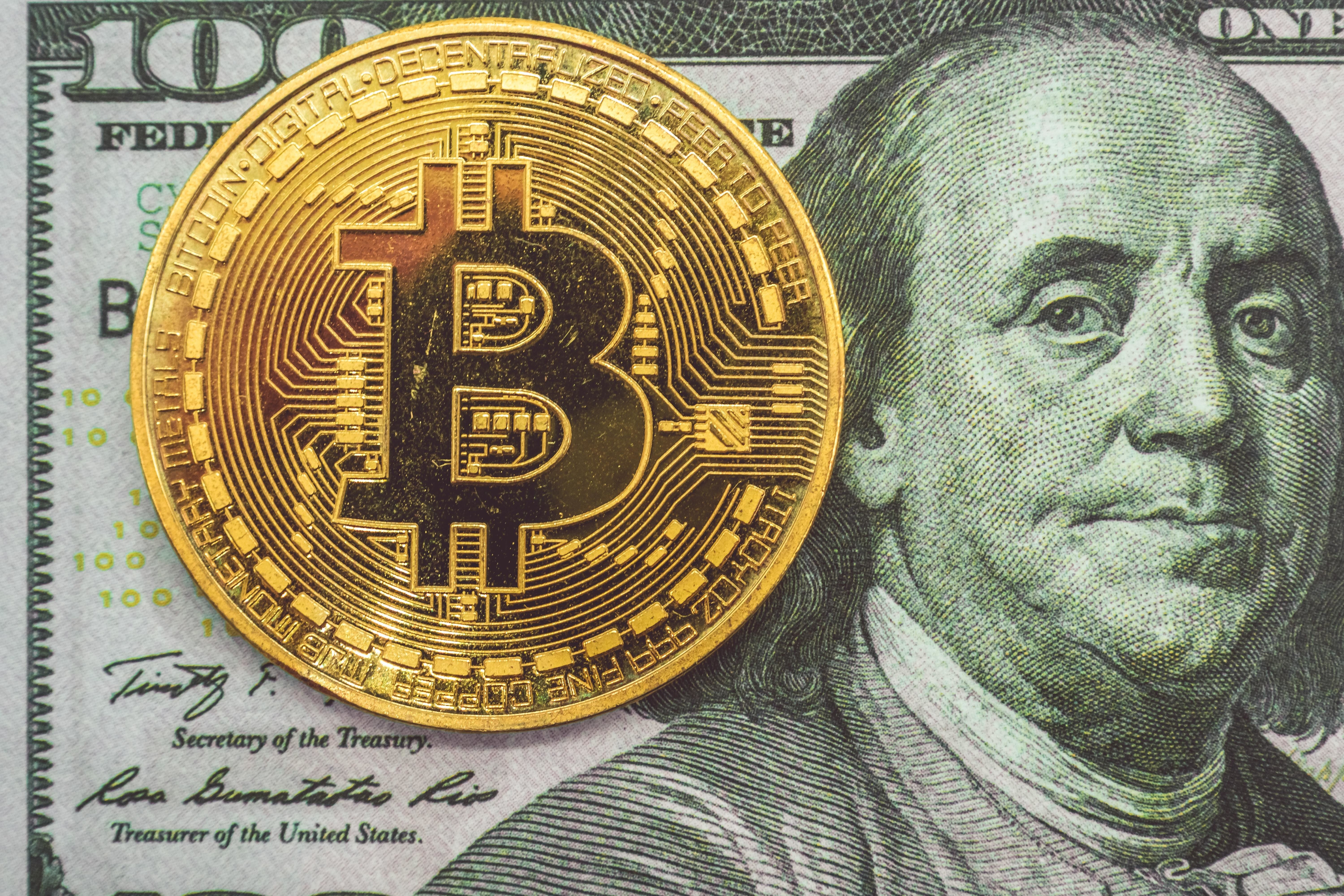 a picture of a bitcoin next to an american one hundred dollar bill featuring bill franklin on the front