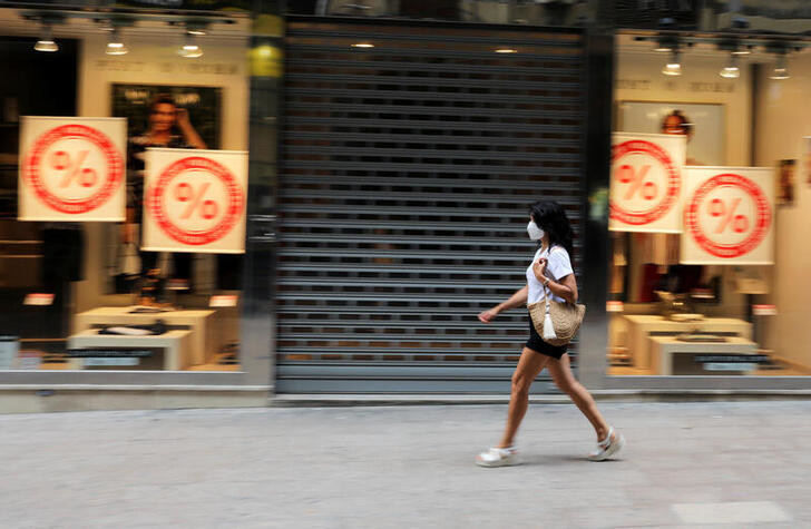 A woman wearing a face mask walks past a closed shop after a judge barred Catalan authorities from enforcing a stricter lockdown to residents in the city of Lleida, to control the coronavirus disease (COVID-19) outbreak, in Lleida, Spain, July 13, 2020. REUTERS/Nacho Doce