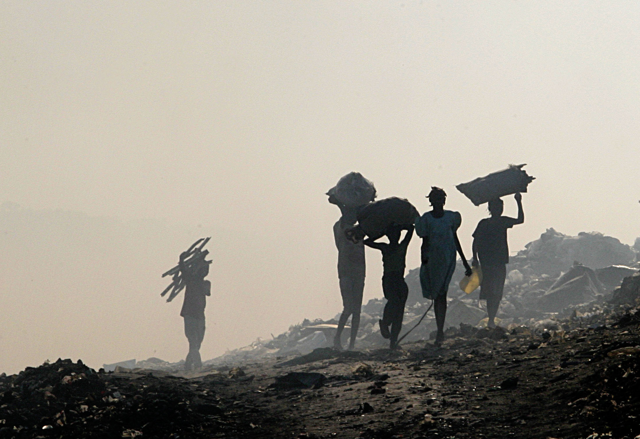 people walk away from the camera carrying debris