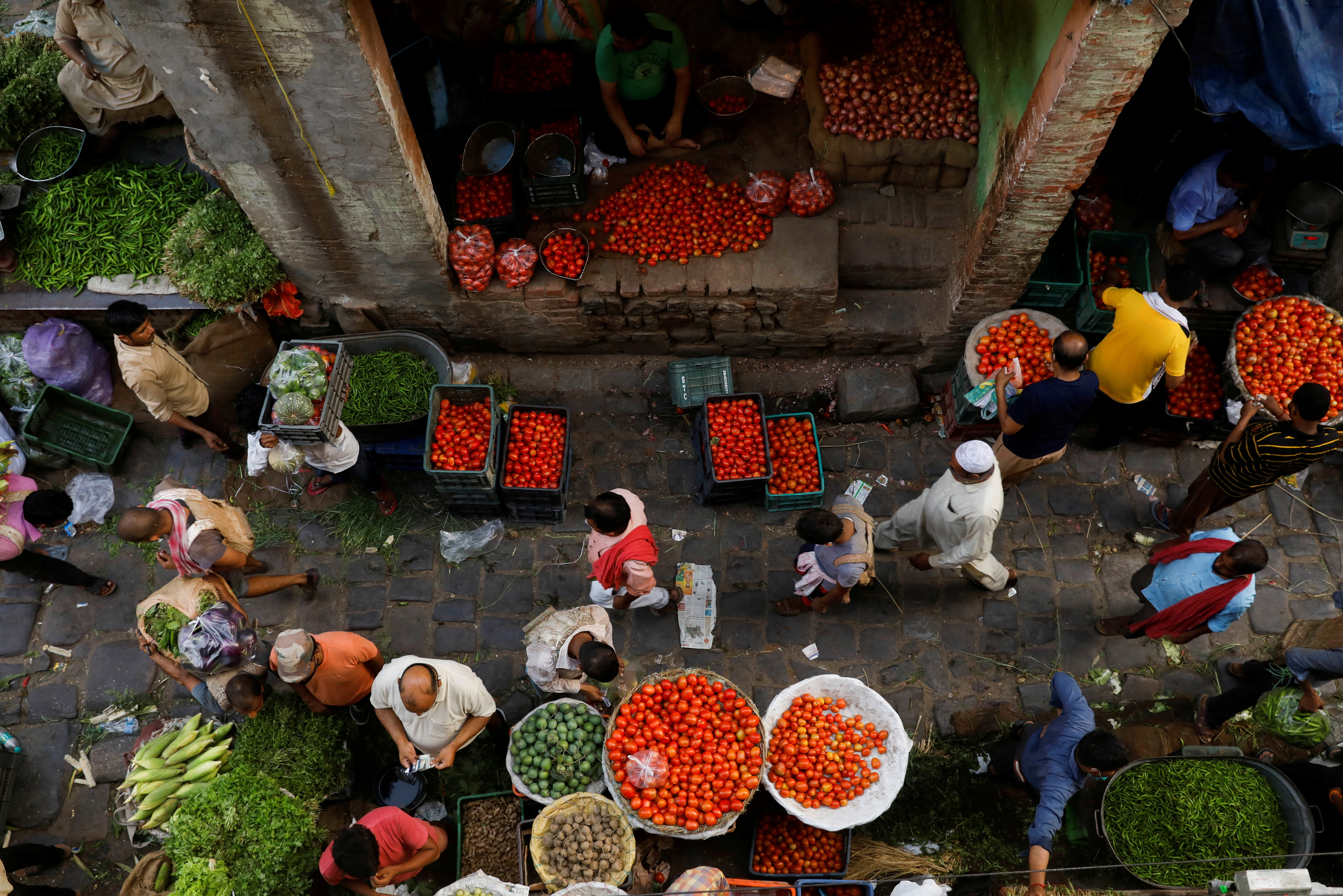 People shop at a crowded wholesale vegetable market after authorities eased coronavirus restrictions, following a drop in the coronavirus disease (COVID-19) cases, in the old quarters of Delhi, India, June 23, 2021. REUTERS/Adnan Abidi     TPX IMAGES OF THE DAY - RC206O9SUYMF