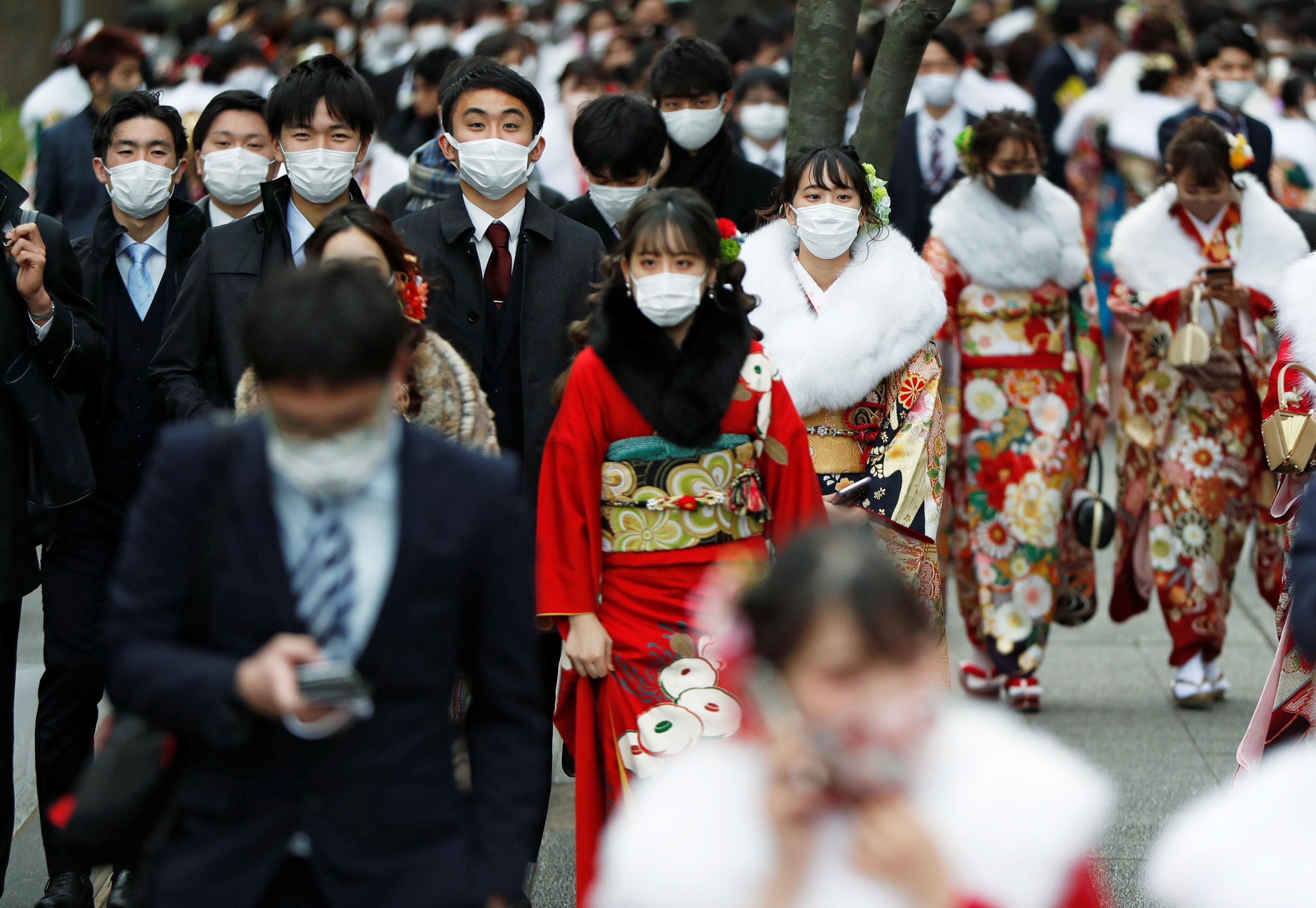 Youth including Kimono-clad women wearing protective face masks attend their Coming of Age Day celebration ceremony at Yokohama Arena after the government declared the second state of emergency for the capital and some prefectures, amid the coronavirus disease (COVID-19) outbreak, in Yokohama, Japan January 11, 2021. REUTERS/Issei Kato - RC2L5L9X2KNT
